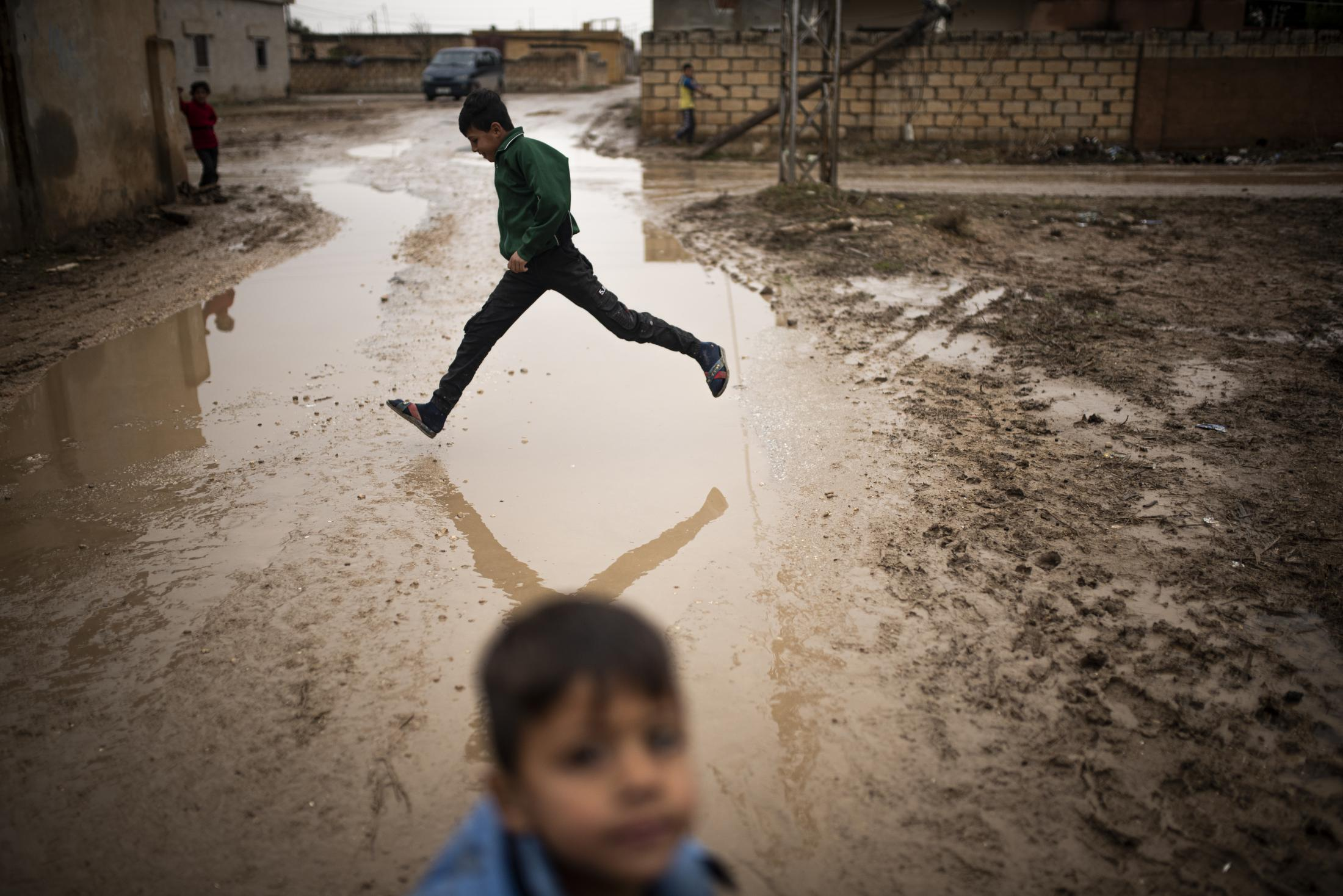 A child jumping a puddle in a street of Tel Nasri near the frontline against yihadists and Turkish Army. After the withdrawal of US troops from northern Syria in October 2019, Turkey launched an offensive against the predominantly Kurdish areas in the northeast of the country along Islamist forces. Calls for war crimes investigations into the conduct of Ankara-backed militias are mounting ever since. (Andoni Lubaki / Euskal Fondoa)