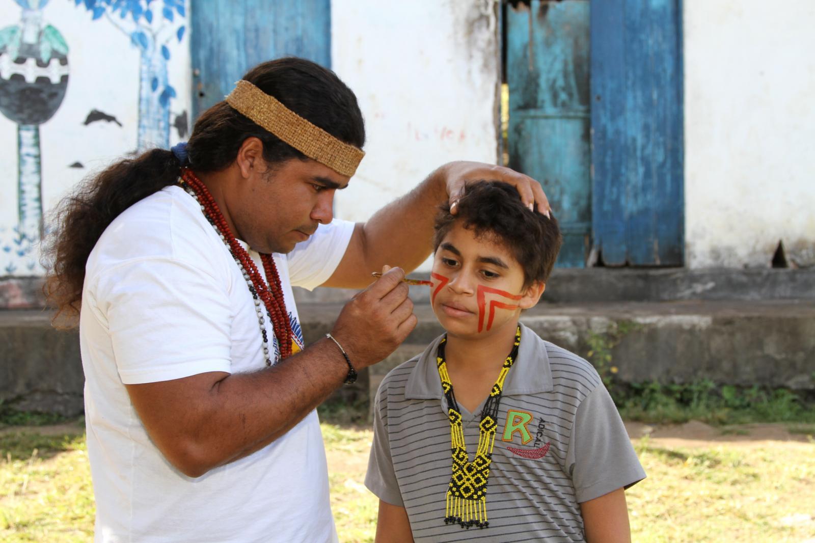 Fábio Titiá, uma liderança dos Pataxós HãHãHãe paints his son face with Urucum paint before a Tore.