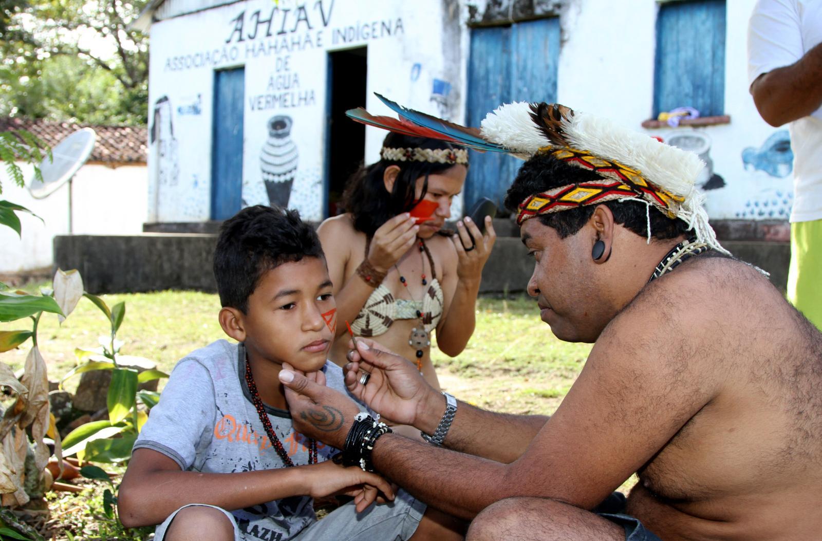 Paulo Titiá, uma liderança dos Pataxós HãHãHãe paints his son face with Urucum paint before a Tore.