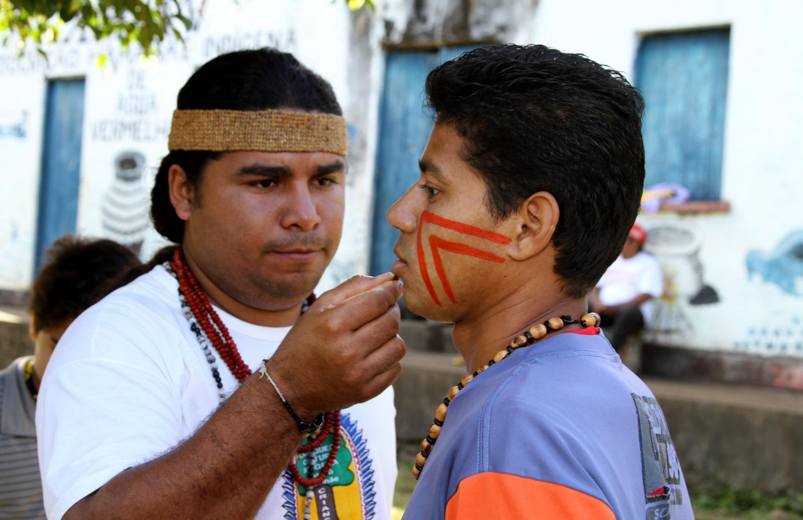 Fábio Titiá, uma liderança dos Pataxós HãHãHãe paints a nephew's face with Urucum paint before a Tore.