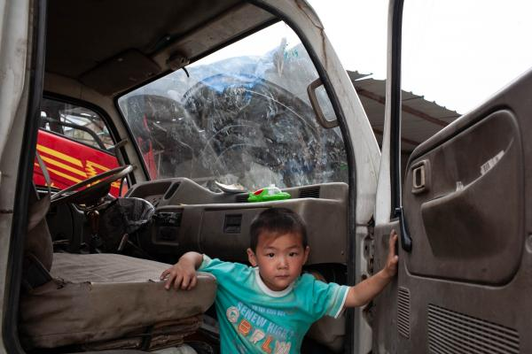 Liu Huan, 5 years old playing in a truck near his father who is repairing truck tire at the Shi Da Road logistic company [2008 Katie Hayes]