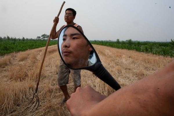 Ding Shijie, 22, left his family farm in Wei Zhuan after middle school to find work in Xian selling meat sticks. His older brother Ding Zhijie is the only son of four who opted to stay and work with his family The two oldest brothers, not pictured, are truck drivers. [2008 Katie Hayes]