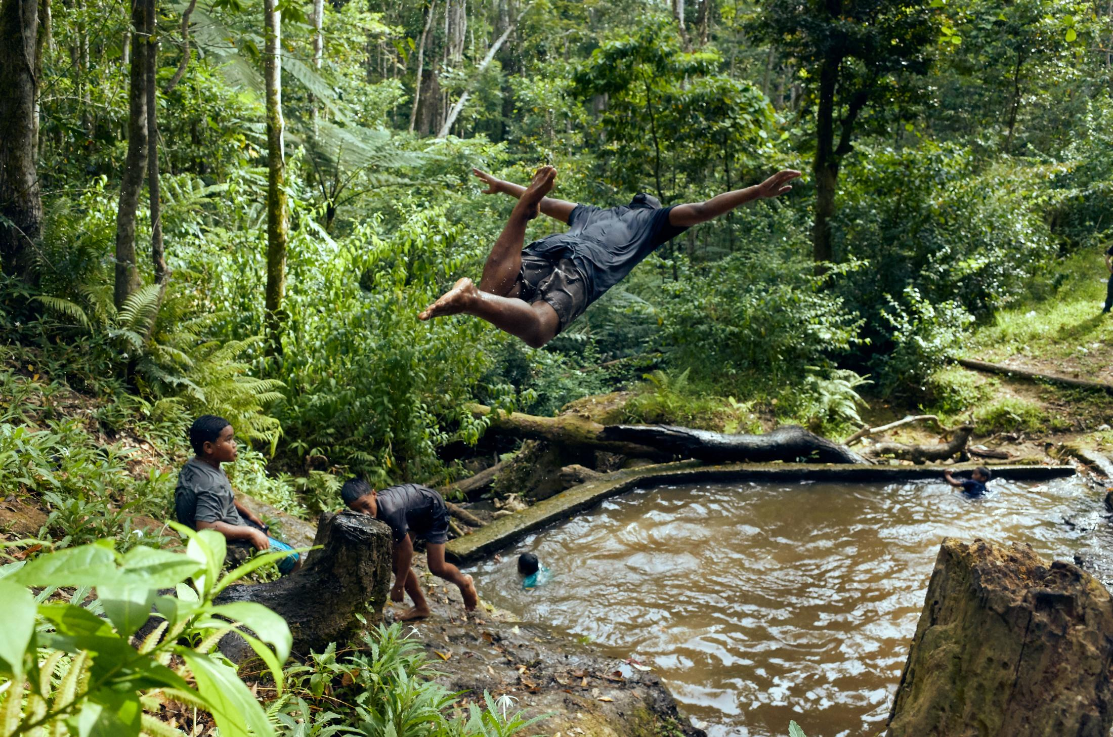 Local youth jumping into a stream on the island of 'Eua. This is the only freshwater tributary in the entire Kingdom of Tonga.