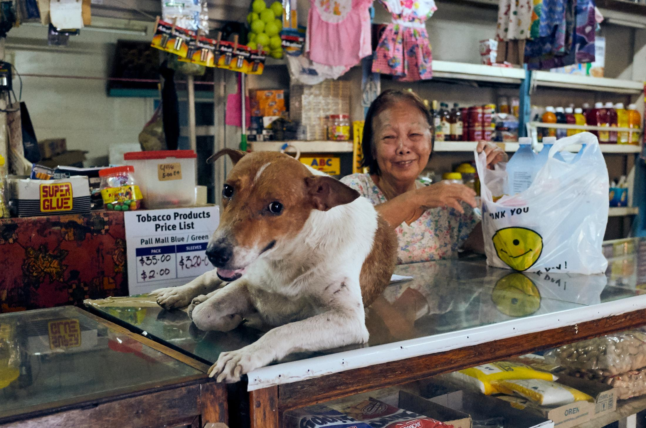 A shopkeeper and her dog in central Auki, Malaita province, Solomon Islands.