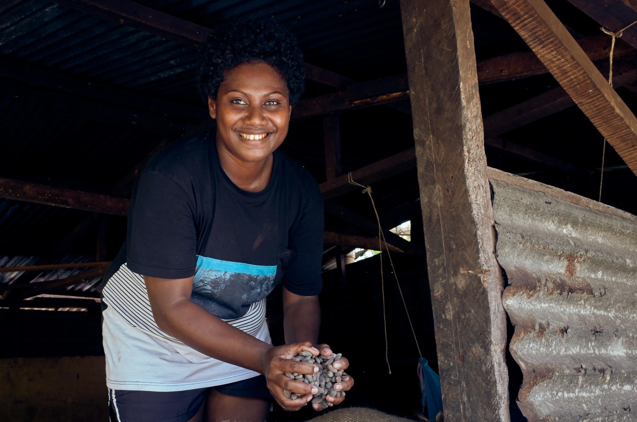 Cocoa processor and community farming association coordinator, Agnes Pilopaso, with a handful of cocoa beans at the Tupaghotua Cocoa Partnership in the Guadalcanal Plains, Solomon Islands.