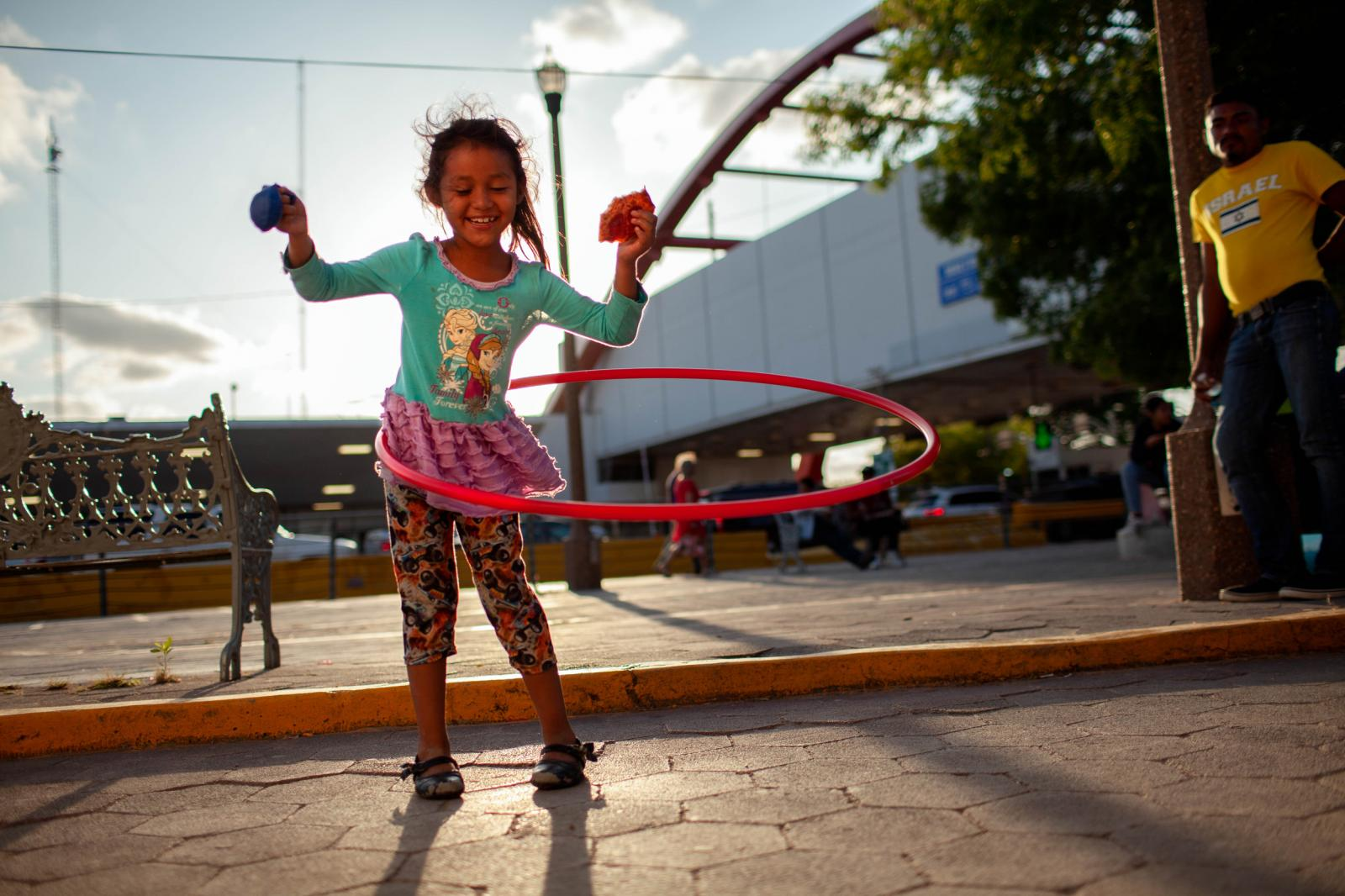 At the base of the International Bridge in Matamoros, Mex, in 2019, families camp, unsheltered for weeks to cross into the United States to have their chance to claim asylum. Here, a girl from Honduras plays with a hula hoop brought by volunteers. Her family waited for a month before being able to cross and join relatives in San Antonio, Tex.