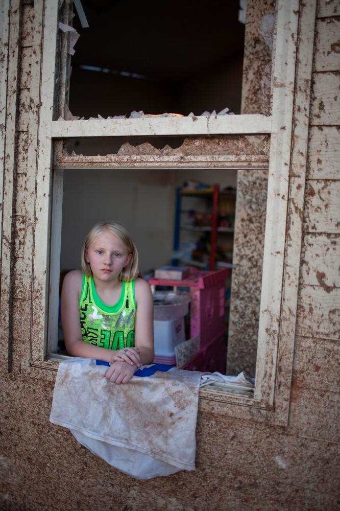 Sara hock, 11, poses for a portrait in her bedroom window at her family's home in the Heatherwood Addition, a subdivision located a mile and a half east of Moore, Okla. Sarah was at school for the tornado, while her father Brian Hock, not pictured, found shelter at a neighbor's storm shelter during the tornado.