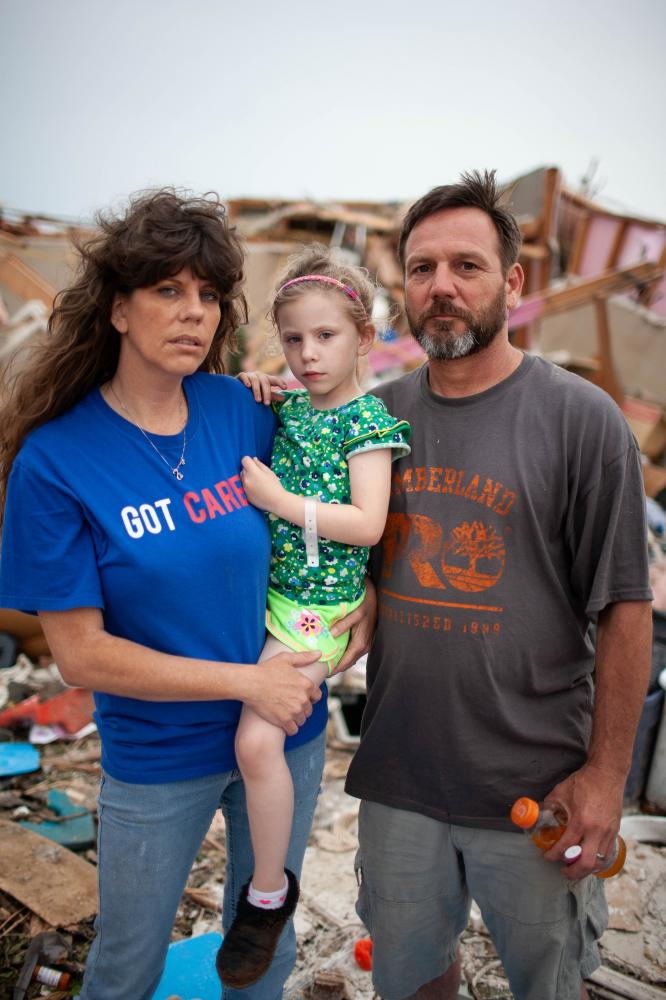 The tornado killed 24 people and caused an estimated $2.2 billion worth of damage. As the community reflects on what happened, one question is: How did so many manage to survive such devastating destruction? Cater (right) took shelter in the family storm shelter with seven neighbors and two dogs. Carter (one name only), his fiance Bree Owens and her daughter Stevee Owens,5, pose for a portrait outside their home.