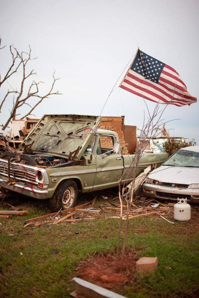 Neighbors hand flags in trees and damaged cars to show solidarity.