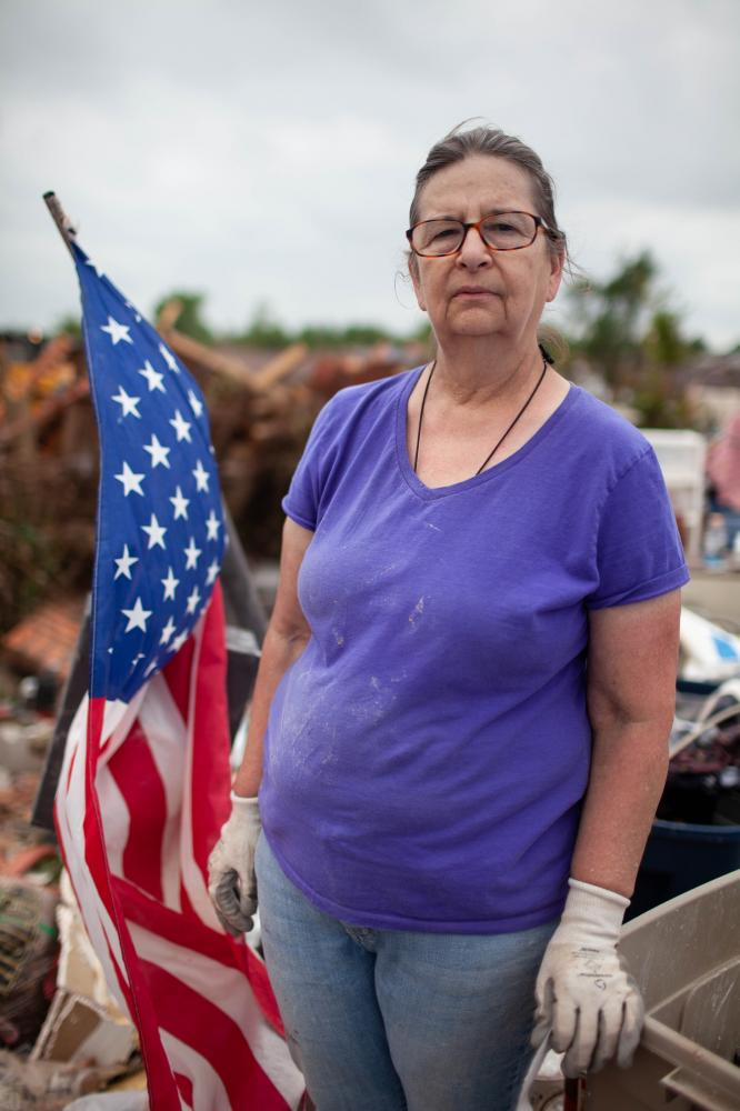 Donna Sidmore watched the tornado on tv from work as it passed over her neighborhood. Her two dogs and four cats, three cats are still missing, were in the house. She does not know any of the volunteers that are swarming over her property. While she is still processing what happened, 20 people came over and started working. She has always hung a flag on her front porch; this one used to hang on the front porch.