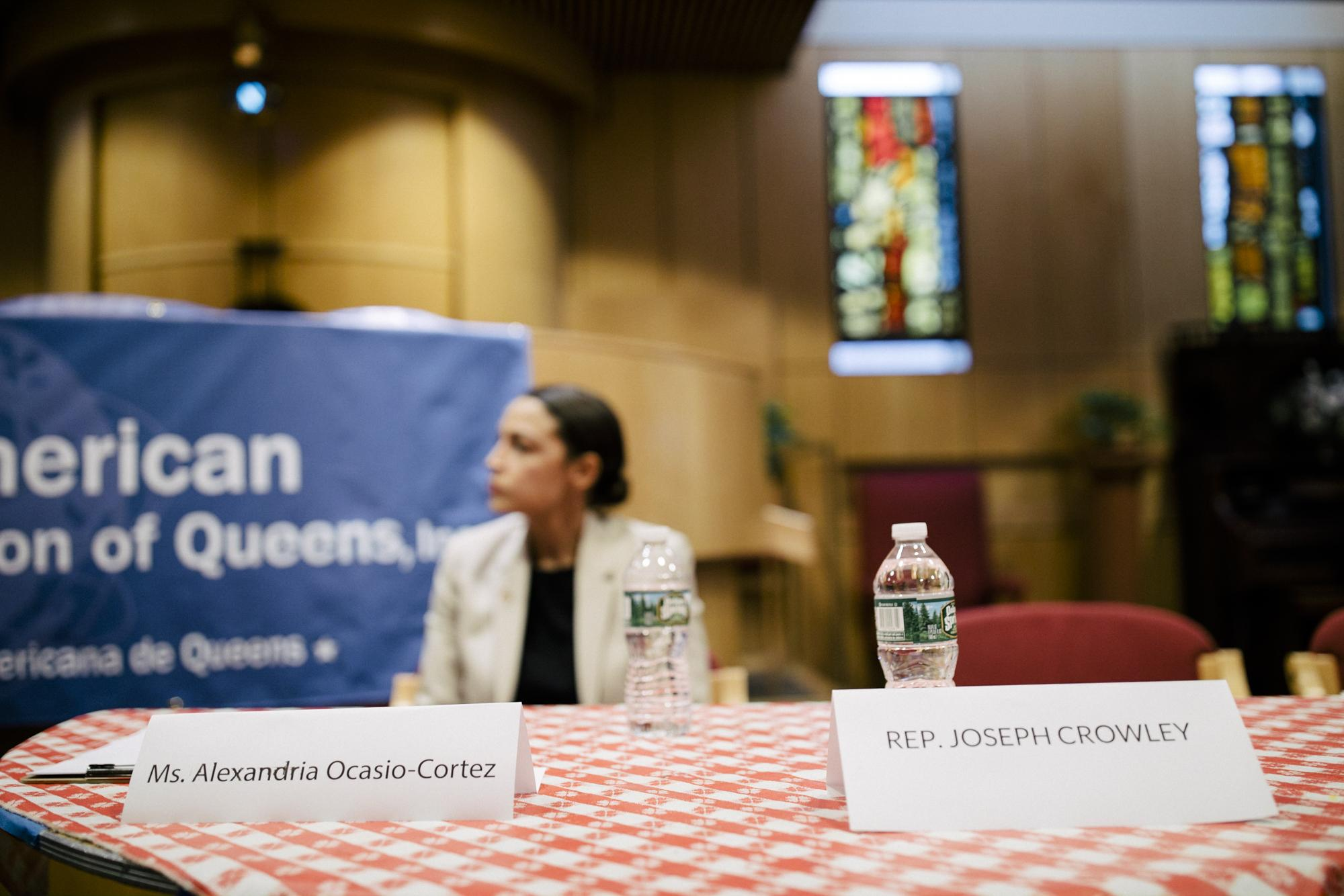 Alexandria Ocasio-Cortez patiently waits for her debate to begin against Congressman Joe Crowley as locals of the Queens neighborhood make their way into the Jewish Center of Jackson Heights, in the Queens borough of New York City, June 11, 2018.