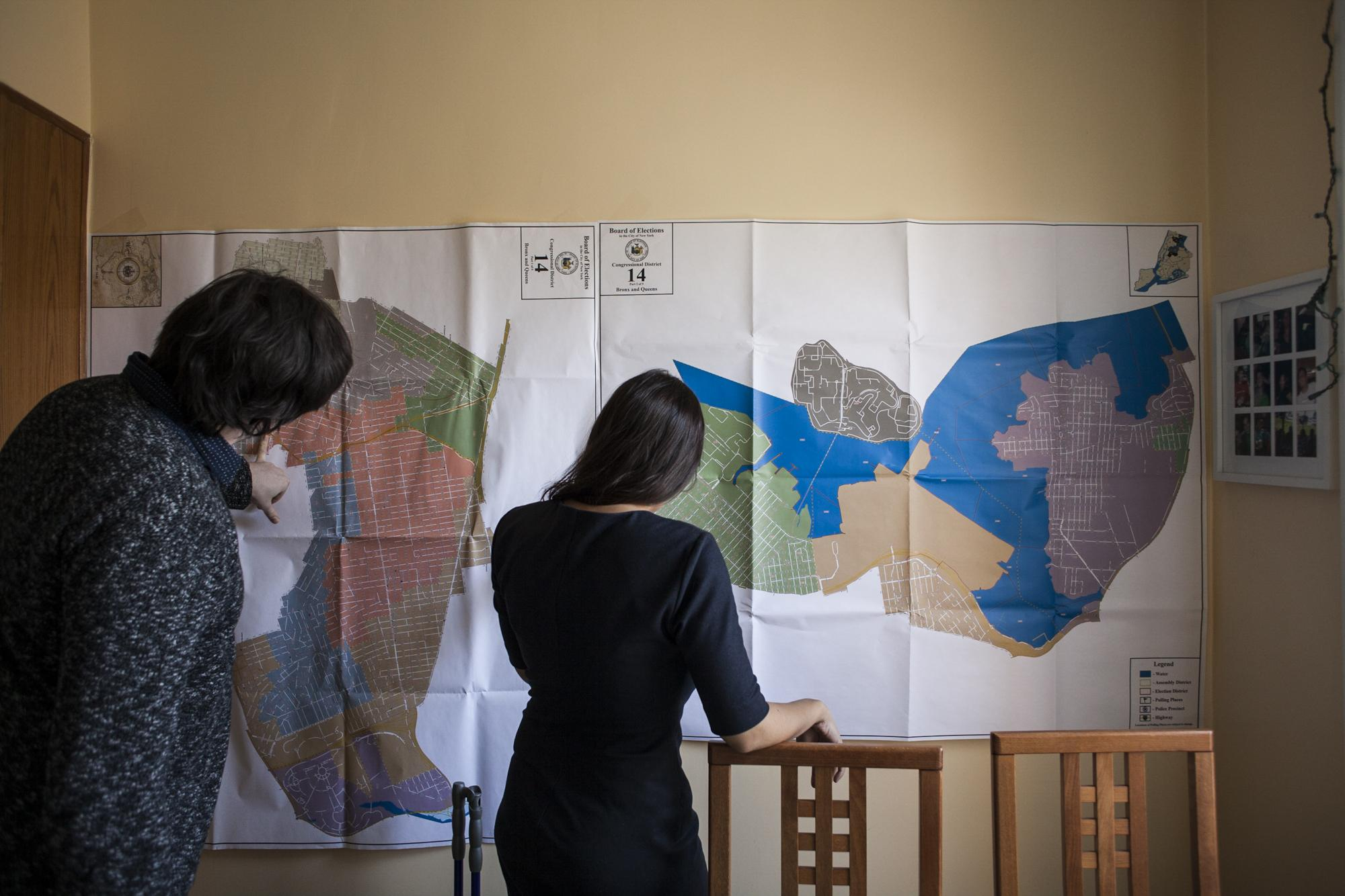 Alexandria and fundraising director for her campaign Michael Carter look over maps of district NY-14 before heading to an event at Lefrak City, in the Queens borough of New York City, April 7, 2018. The event was a discussion on how the community should move forward after the Board of Elections had filed an appeal to move the polling site in Lefrak City's continental room, a location in Lefrak City that has been the communities polling site for nearly 50 years.