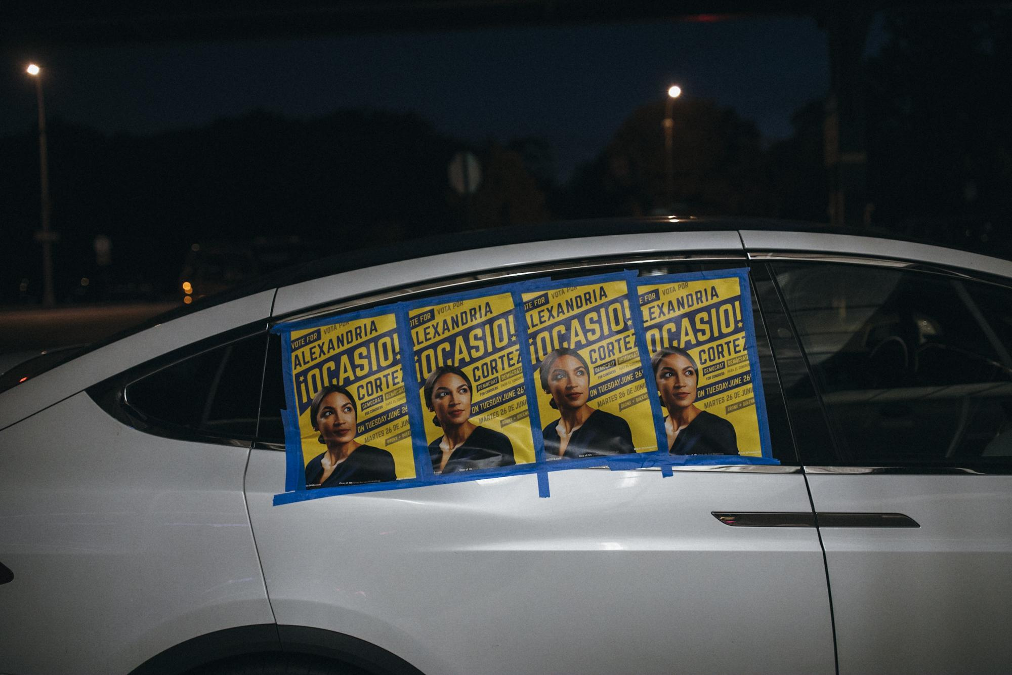 """A car displays posters of congressional candidate Ocasio-Cortez on its windows as volunteers and supporters make their way into the NY-14 Primary """"Watch Party"""" at Park Billiards Cafe and Sports Bar, in The Bronx borough of New York City, June 26, 2018."""