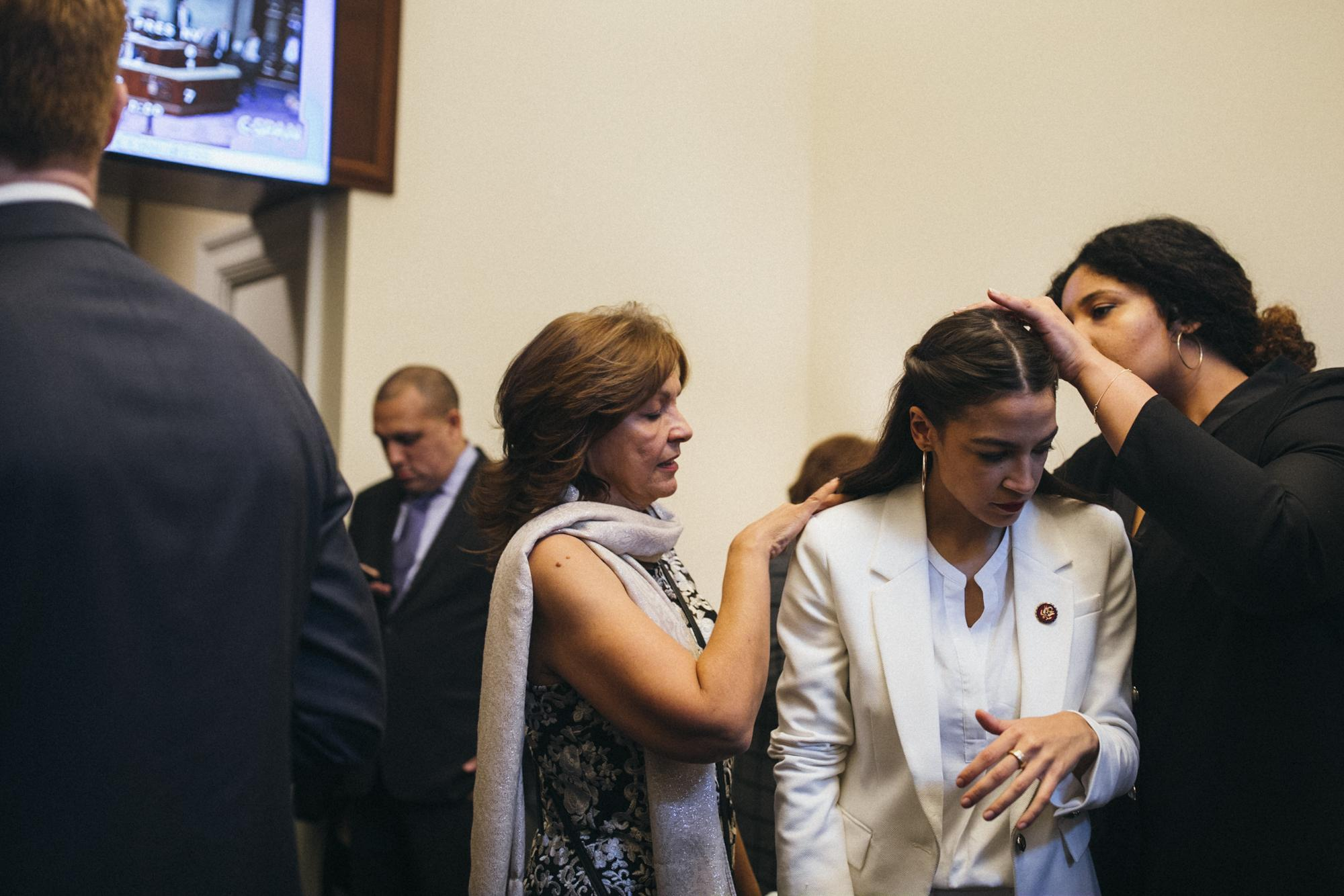 Congresswoman Alexandria Ocasio-Cortez, center, has her hair braids put back into place before she is off to take the oath of office by her Mother, Blanca, left, as she is surrounded by supporters who made the five-hour bus trip from her district, in the Cannon House Office Building, Washington D.C. District of Columbia, United States of America, January 3, 2019.