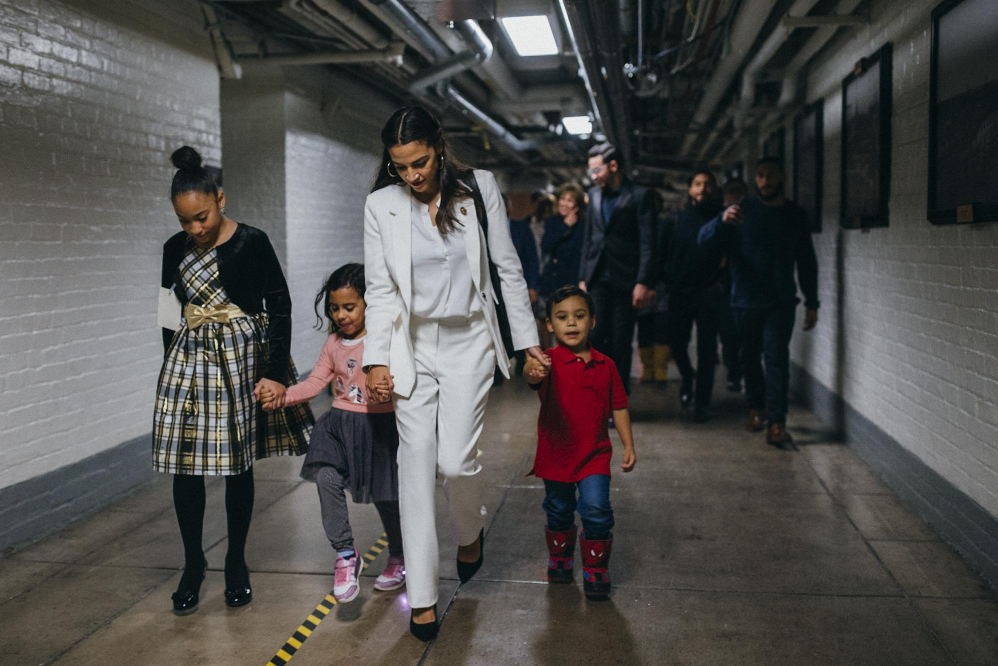 Congresswoman Alexandria Ocasio-Cortez, center, is accompanied by loved ones as she navigates the underground tunnels of the United States Capitol Complex to take the oath of office, in Washington D.C. District of Columbia, United States of America, January 3, 2019. Seizing an opportunity to shine a light on history, Rep. Alexandria Ocasio-Cortez wears an all-white suit as an homage to the brave women of the United States of American who fought for the 19th Amendment, a women's right to vote.
