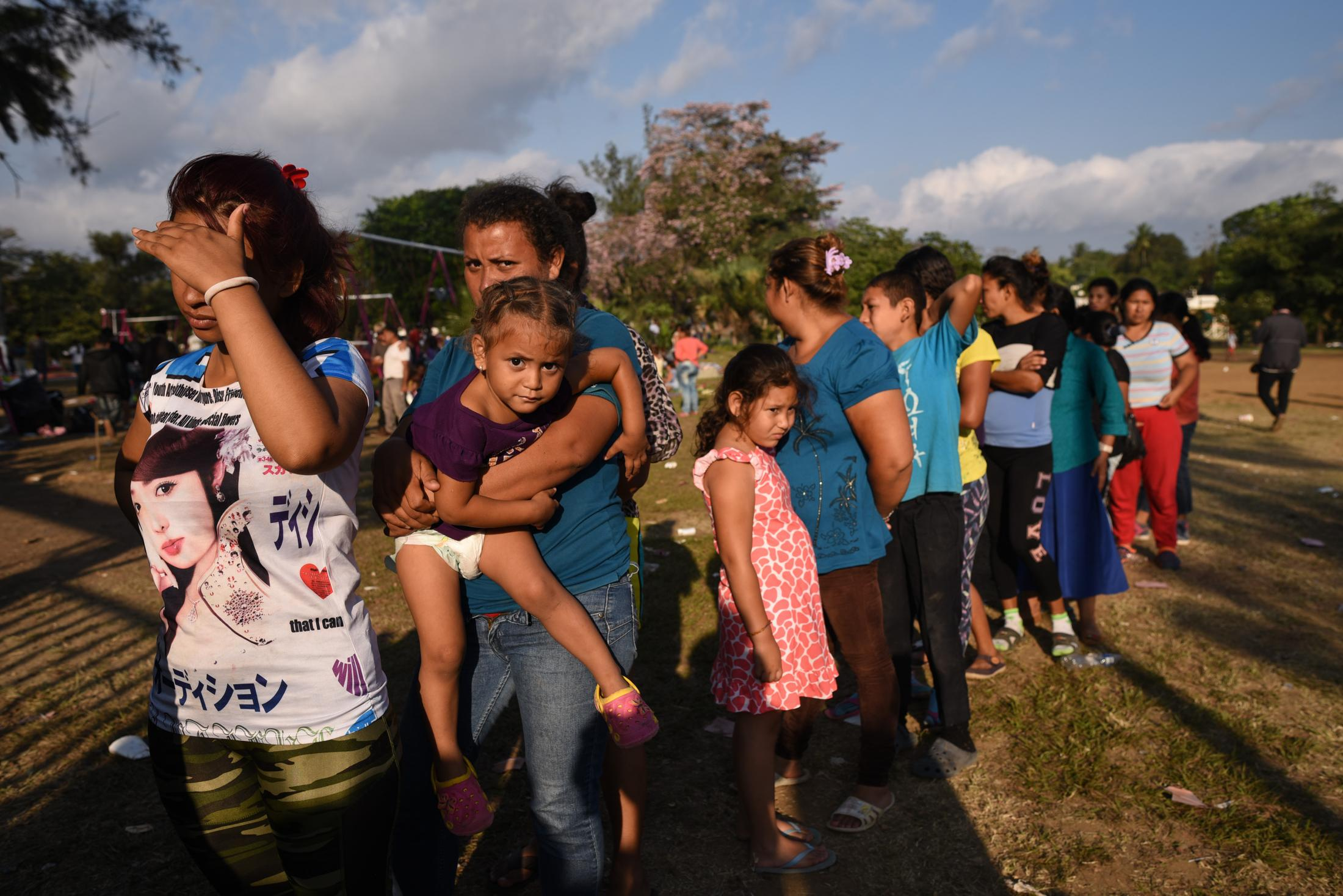Mujeres y niños migrantes se forman para recibir alimentos en un centro deportivo de Matías Romero, Oaxaca. El 3 de Abril del 2018.