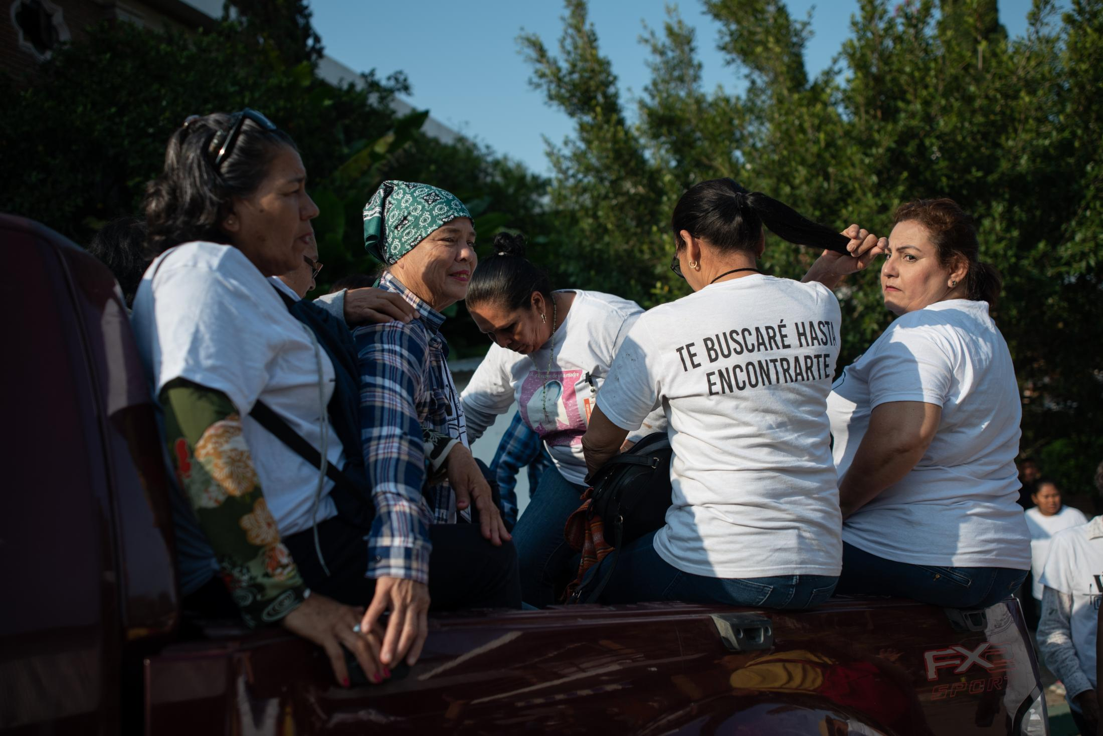 """The seekers collective """"Las Rastreadoras del Fuerte"""" from Sinaloa, Mexico, board a pickup truck inside the Casa de la Iglesia center, where they housed about 300 people associated with social groups who participated in the fifth National Missing Persons Search Brigade, on February 20, 2020 in Papantla, Veracruz, Mexico, on February 20, 2020. Victoria Razo for NPR"""