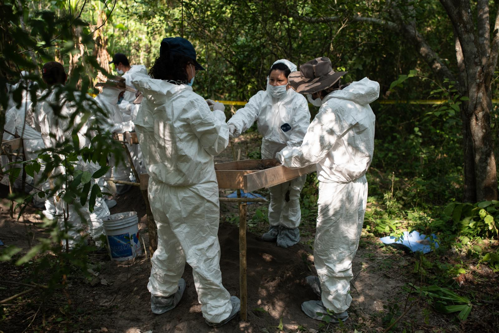 "A group of relatives of missing persons and forensic experts work inside the ranch ""La Gallera"" where human remains have been located during the fifth National Missing Persons Search Brigade in Tihuatlán, Veracruz, Mexico, on February 20, 2020. Victoria Razo for NPR"