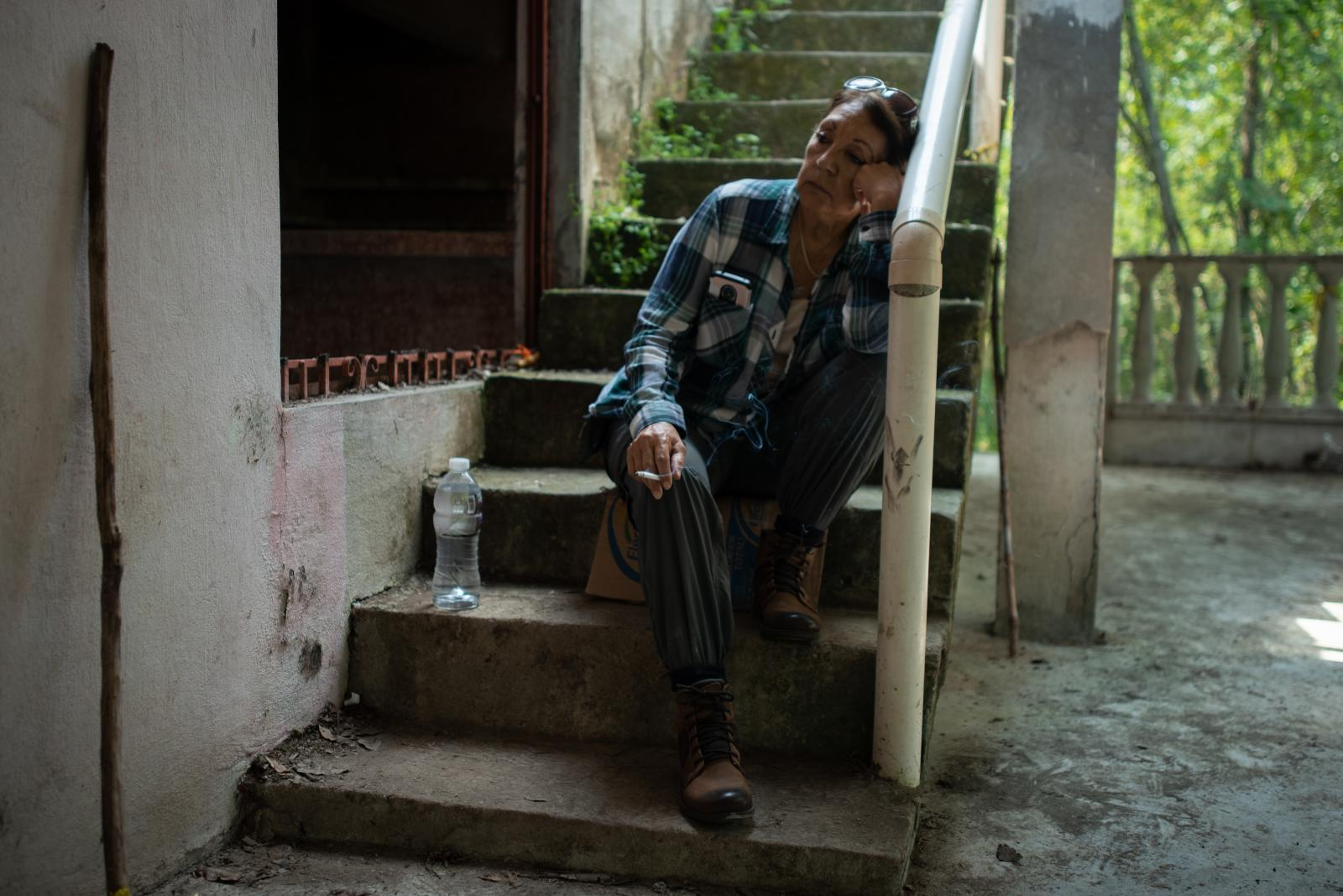 "Teresa Figueroa, 66, seeker from Baja California, Mexico, rests inside the house located in the ranch ""La Gallera"" where human remains have been located during the fifth National Missing Persons Search Brigade in Tihuatlán, Veracruz, Mexico, on February 20, 2020. Victoria Razo for NPR"