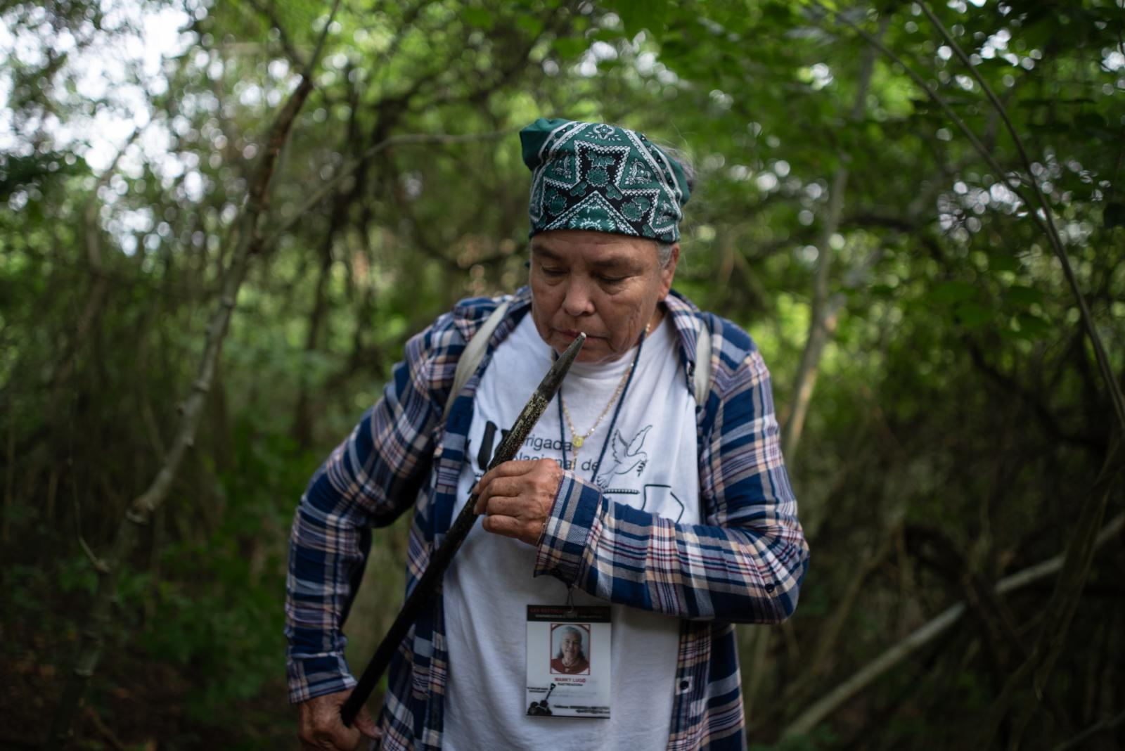 Manky Lugo, 64, seeker for missing persons of Sinaloa, Mexico, smells a metallic tool that buried in the earth in field that is investigated by police authorities and family groups participating in the fifth National Missing Persons Search Brigade in Tihuatlan, Veracruz, Mexico, on February 20, 2020. Victoria Razo for NPR