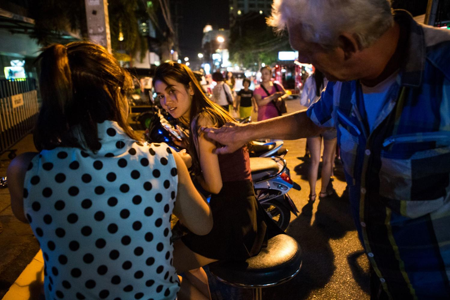 A tourist harasses a woman outside of a bar in Chiang Mai, Thailand