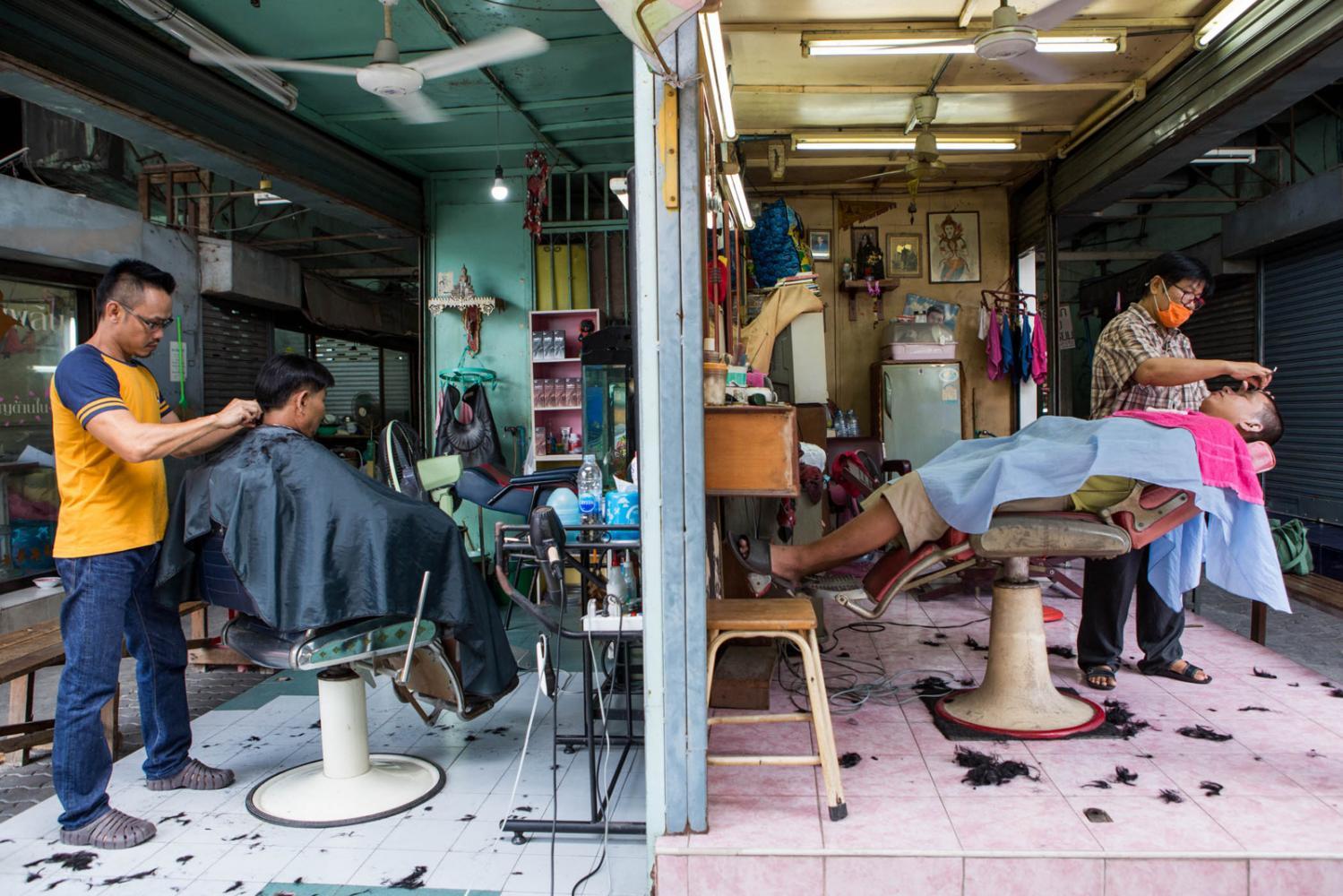 Barber shops under a bridge in Bangkok, Thailand