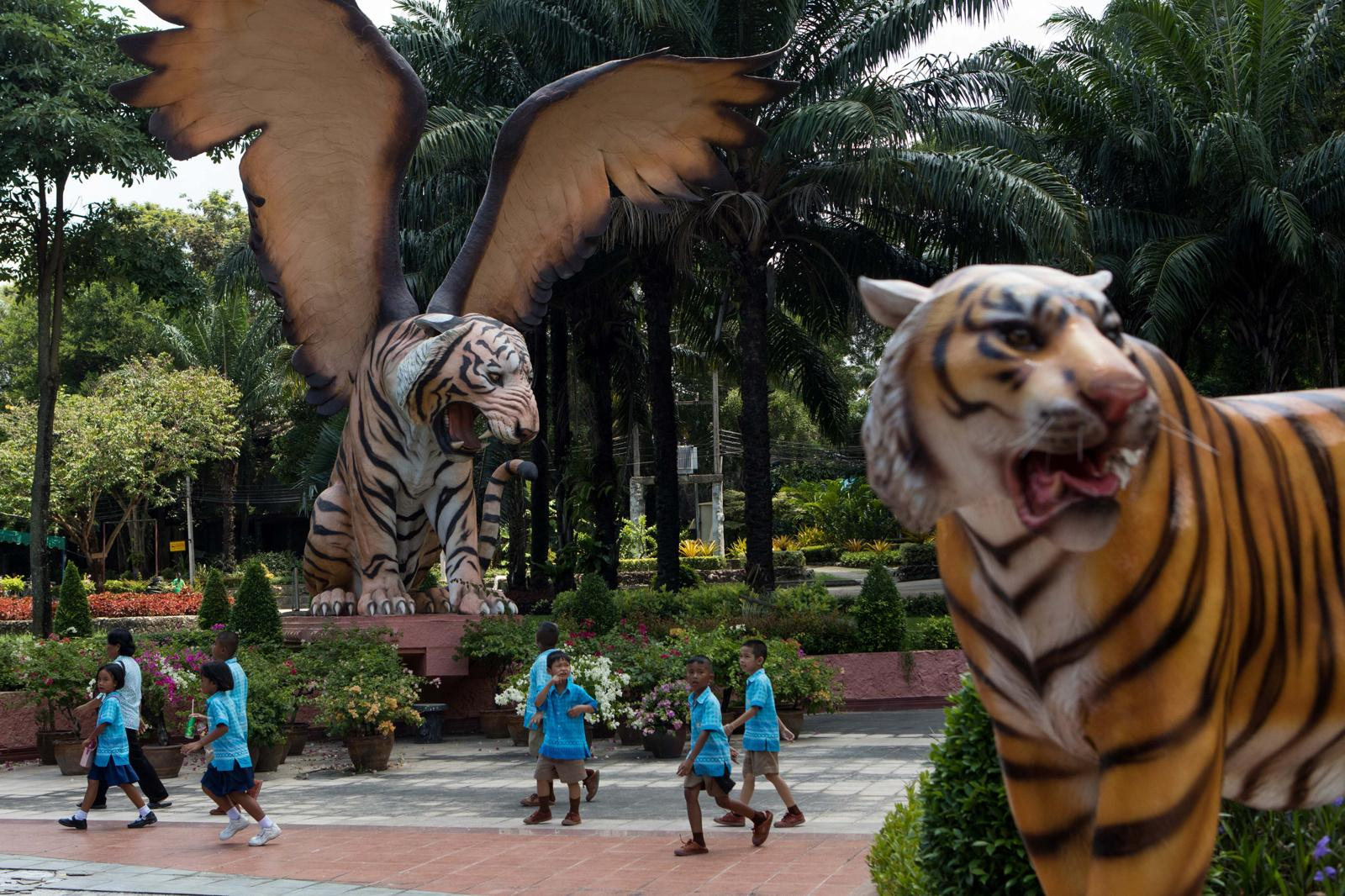 Pattaya, Thailand � September 28, 2018 : Schoolchildren walk by large statues at the Sriracha Tiger Zoo. Credit: Amanda Mustard for New York Times