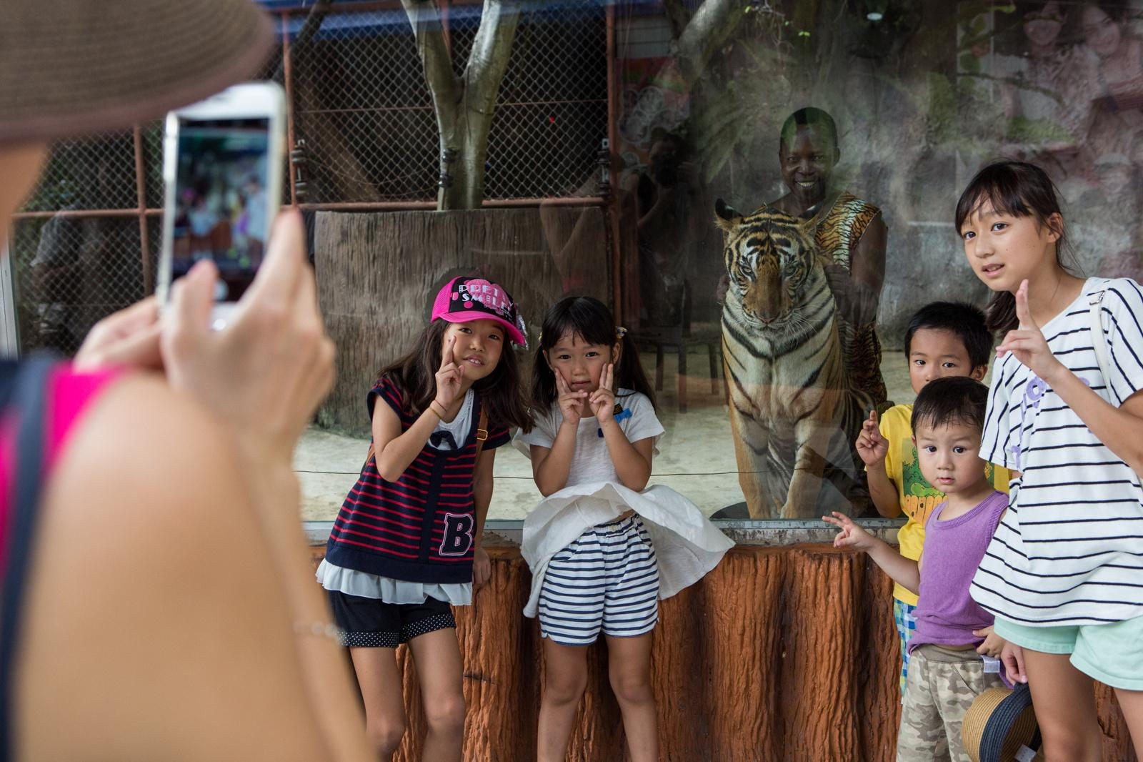 March 30, 2016 - Sriracha, Thailand - Tourists pose for a photo with Tony, a Kenyan man who plays a character role at the Sriracha Tiger Zoo. Tony moved to Thailand in the 1980's as a circus performer. He loved animals, and proposed this role to the zoo as a new career for himself. He lives in Sriracha with his wife and children. Photo by Amanda Mustard for the New York Times