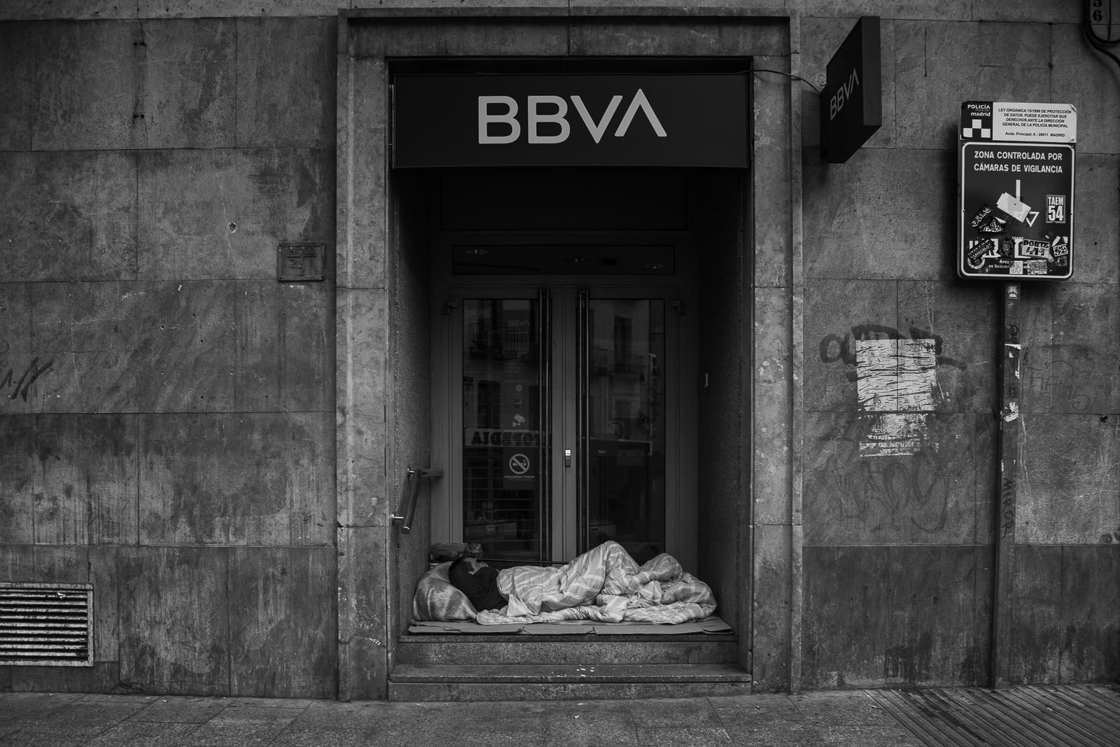 Indigent sleeping at the door of the BBVA bank in the city of Madrid during the national lockdown amid coronavirus pandemic.