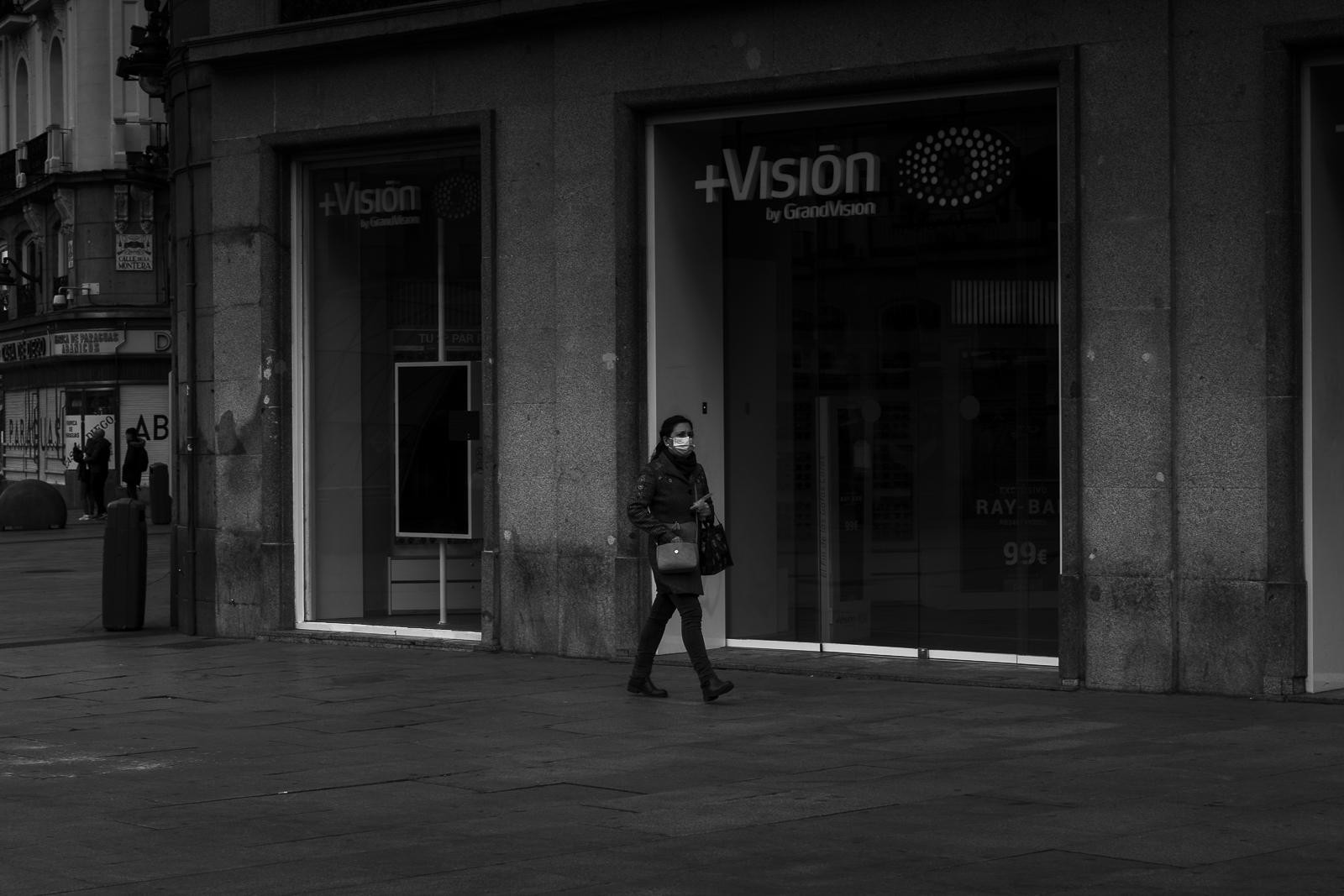 A woman protecting herself with a mask walks in Plaza Sol one of the most imortant turistic places of Madrid city center durinfg the national lockdown amid coronavirus pandemic.