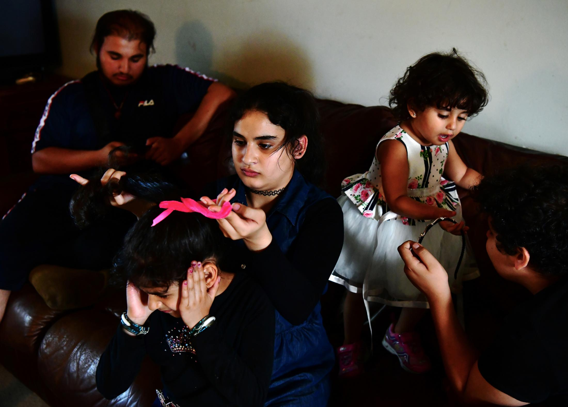 Narjes Al Hraishawi, 14, ties her younger sister's, Fatima's, hair Asinat, right, 2, tries to grab her headband from her older brother, Ali, 12. Abbas, left, 17, watches Youtube videos before driving two of the children to a carnival. The family's children range from 17 to a year and a half.