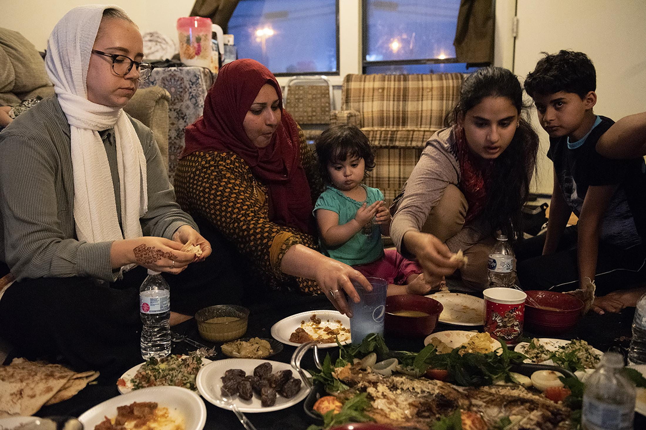 The Al Hraishawi family and Toni, a family friend and translator, break their fast on the last day of Ramadan on Monday, June 3, 2019, at the families home. It was one of the last nights that their father was there before he left again to work in Iraq.