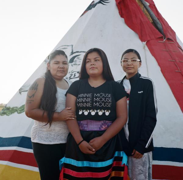 """Prairiedawn Thunderchild (right), 16, with her sister Tahnee Thunderchild (center), 14, and their mother, stand for a portrait at the Wolf Point pow wow on Fort Peck Indian reservation. The sisters were almost abducted a year ago by a vehicle of oil workers in Wolf Point. The family has since moved to a safer location. """"They chased us around in the car…[they] probably wanted gross things from us"""" Tahnee said."""
