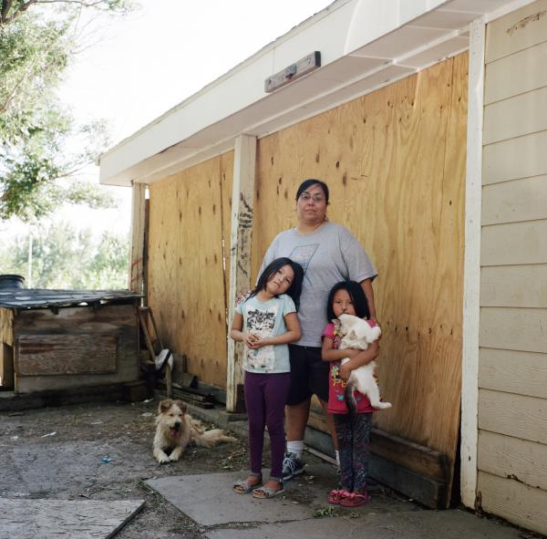 Tara Douglas Ricker, 44, with her two grand-daughters outside of her home in Wolf Point on Fort Peck Indian Reservation. One of Tara's brothers, Valen Hotomanie, remains missing today, while her other brother, Clair Fourstar, was found dead in the Missouri River. She worries for her grand-daughters, she has seen an increase in drugs and has heard stories of sex trafficking.