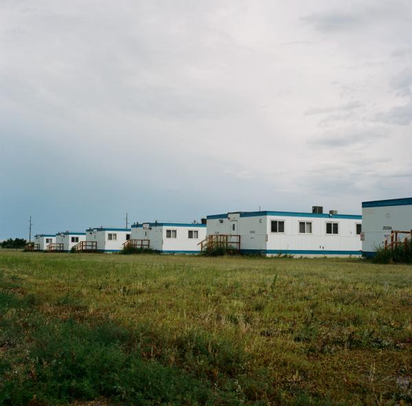"""An abandoned """"man camp"""" which provides housing to temporary oil workers near Trenton, North Dakota. Oil employees come in the thousands, with disposable income, and are often subjected to difficult working conditions. The Department of Justice state that: """"oil industry cmaps may be impacting domestic violence, dating violence, sexual assault, and stalking in the direct and surrounding communities in which they reside."""""""
