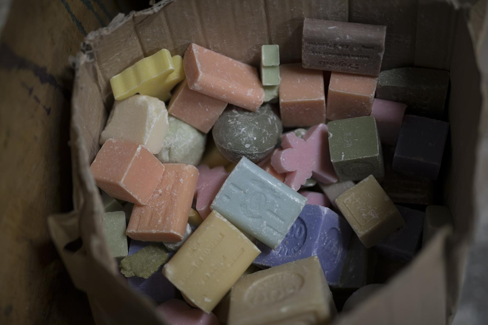 Discarded bars of soap sit in a bucket at the Marseille Licorne soap factory, southern France, Monday, March 16, 2020. (AP Photo/Daniel Cole)
