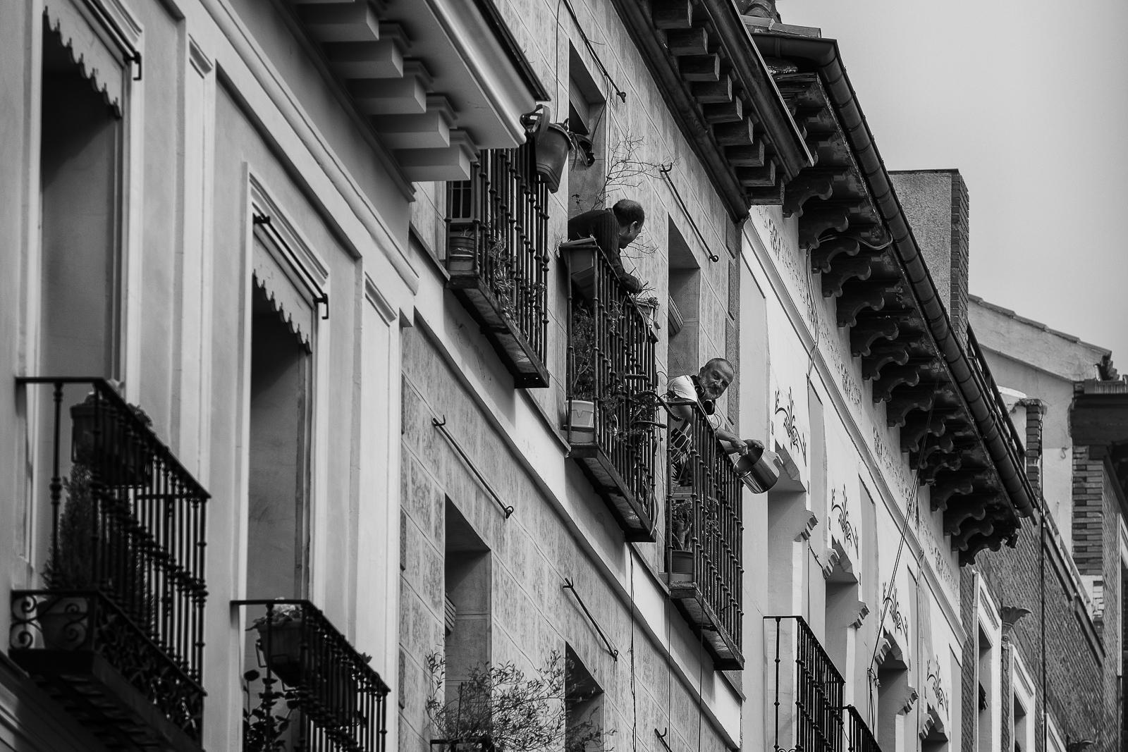 Two men talking from balcony to balcony during the coronavirus lockdown in Madrid city center.