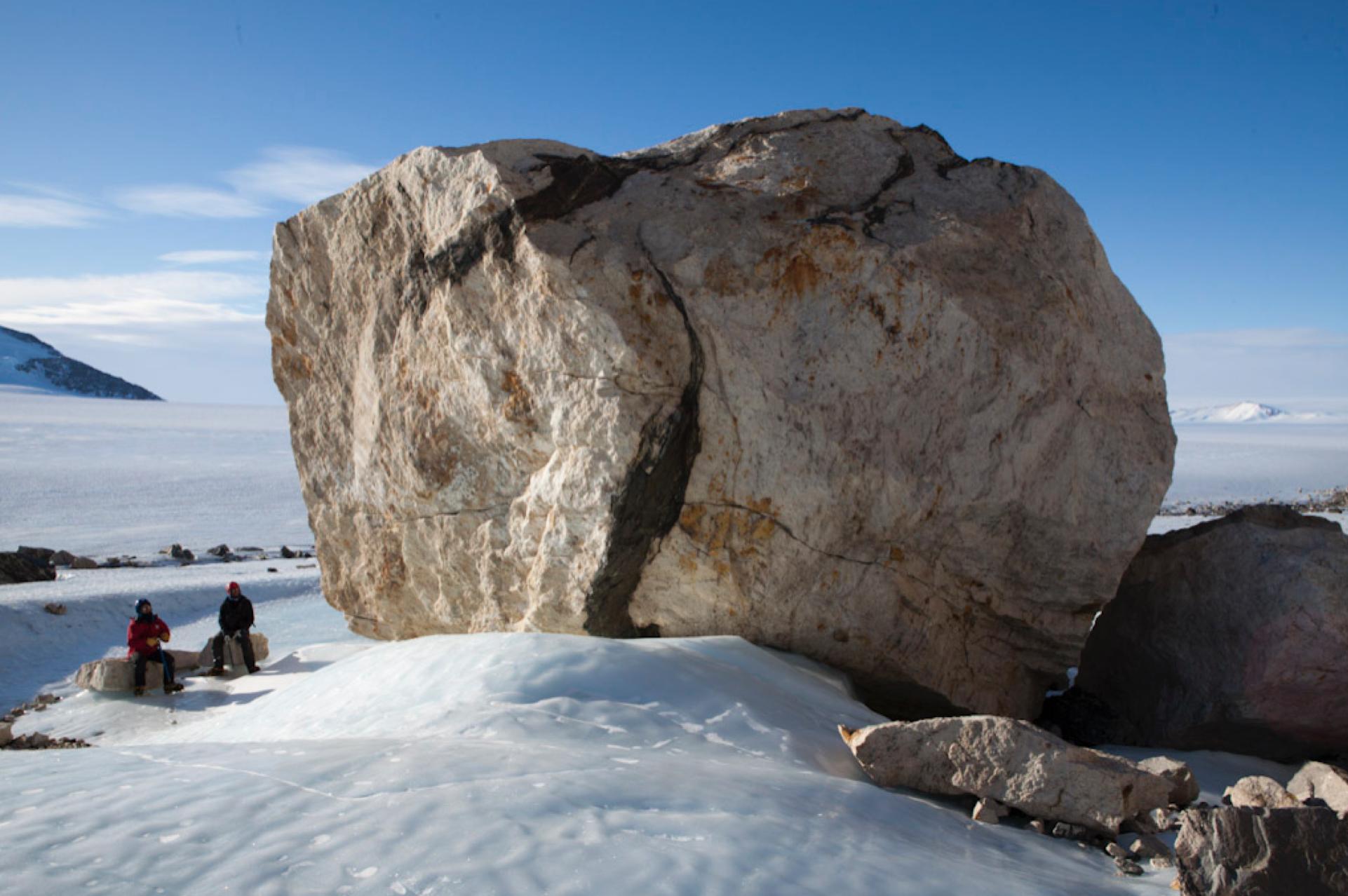 A glacial erratic boulder sititng on a glacier.