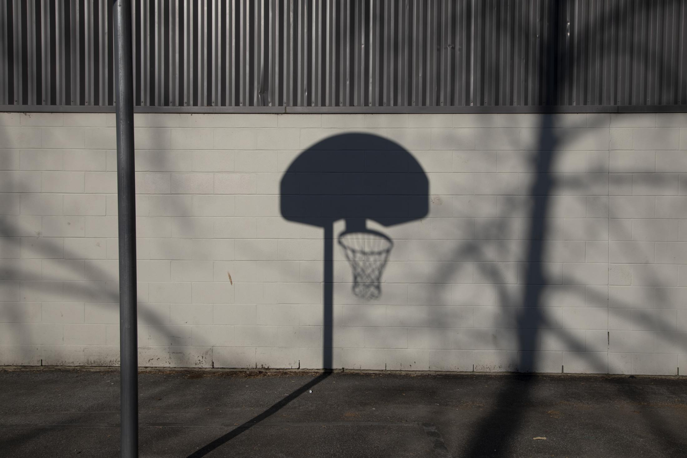 The shadow of a basketball hoop is seen at Carson Graham Secondary School in North Vancouver, B.C., on Friday, March 20, 2020. Effective Friday, March 20, 2020, the City and District of North Vancouver have closed all playgrounds and playing fields in an attempt to curb the spread of COVID-19. North Vancouver has been a hotspot of COVID-19, with ten deaths connected to the Lynn Valley Care Centre as of Monday, March 23, 2020.