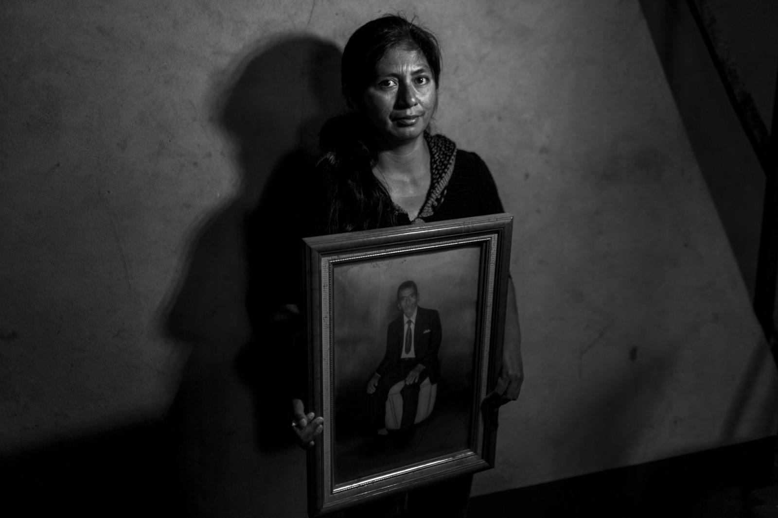 Zoraida Pozo Morales, quien perdió a su madre, abuelo y tíos,posa con el retratode su abuelo Claudio durante el velorio en Ocros, Ayacucho.