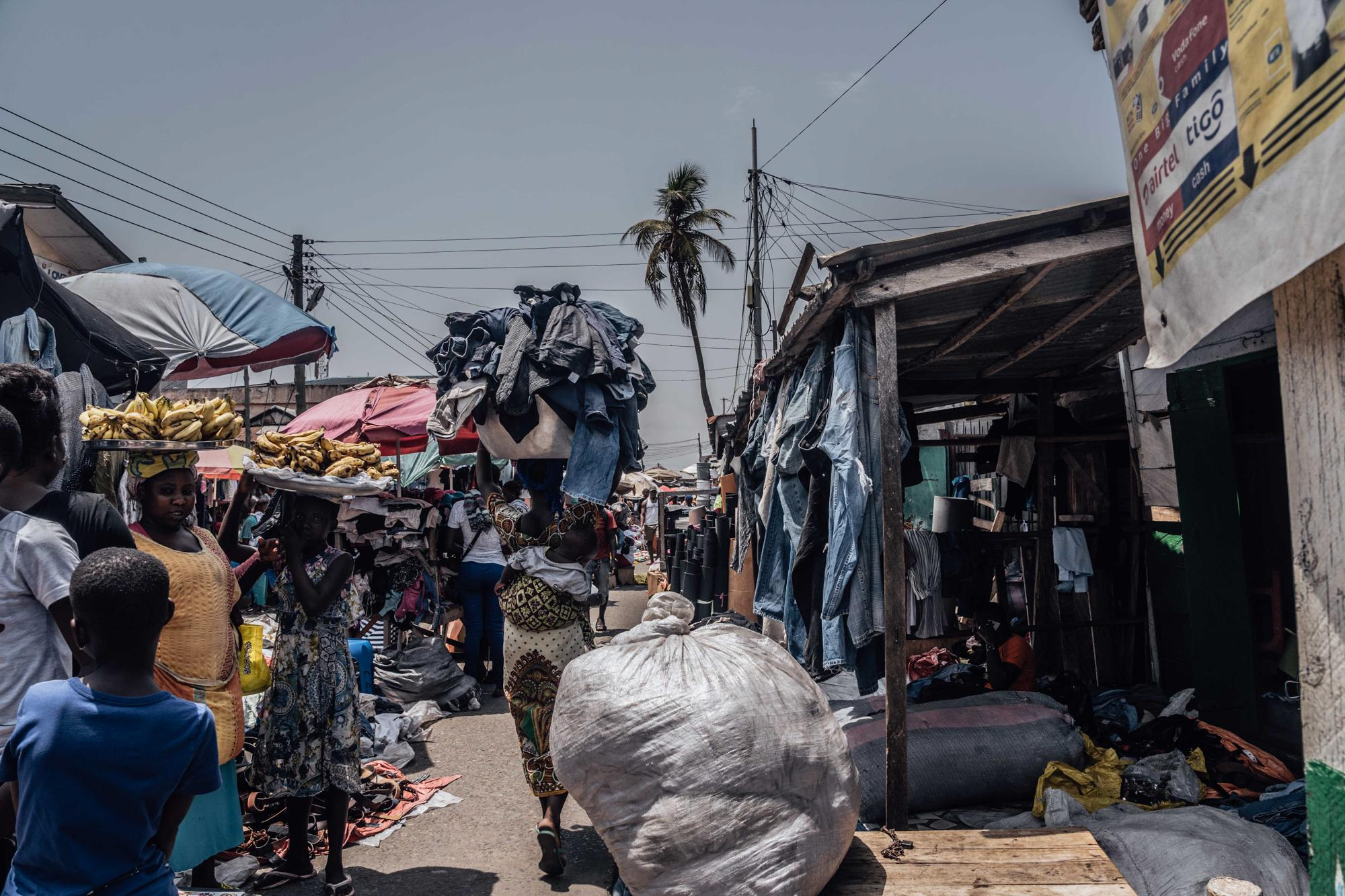 Asana carries a load with her son wrapped at the back in the sweltering heat of Accra's market.