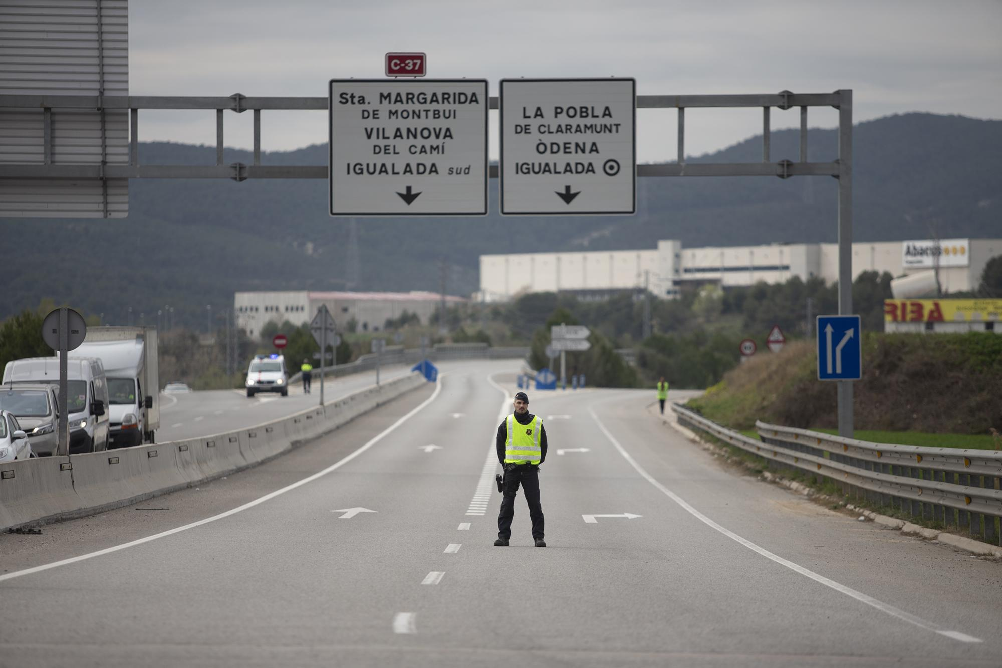 A mosso de esquadra police officer stands on the closed off road near Igualada, Spain, Friday, March 13, 2020. Over 60,000 people awoke Friday in four towns near Barcelona confined to their homes and with police blocking roads. The order by regional authorities in Catalonia is Spain's first mandatory lockdown as COVID-19 coronavirus infections increase sharply, putting a strain on health services and pressure on the government for more action.  (AP Photo/Joan Mateu)