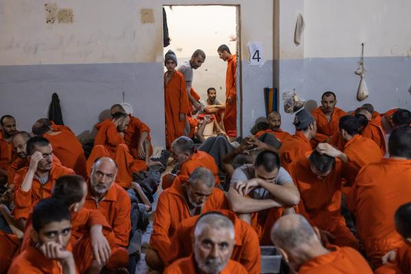 Le 30 octobre 2019, Nord Est de la Syrie. Une prison abrite des supposés membres de Daesh. Environ 5000 détenus vivraient ici. La prison est ouverte depuis 4mois. Elle est surpeuplée. Voici une des nombreuses cellules, pouvant contenir une centaine de prisonniers.. Les fenêtres ont été condamnées. Il y a donc très peu de lumière du jour. Au fond, un enfant dans l'encablure de la porte.