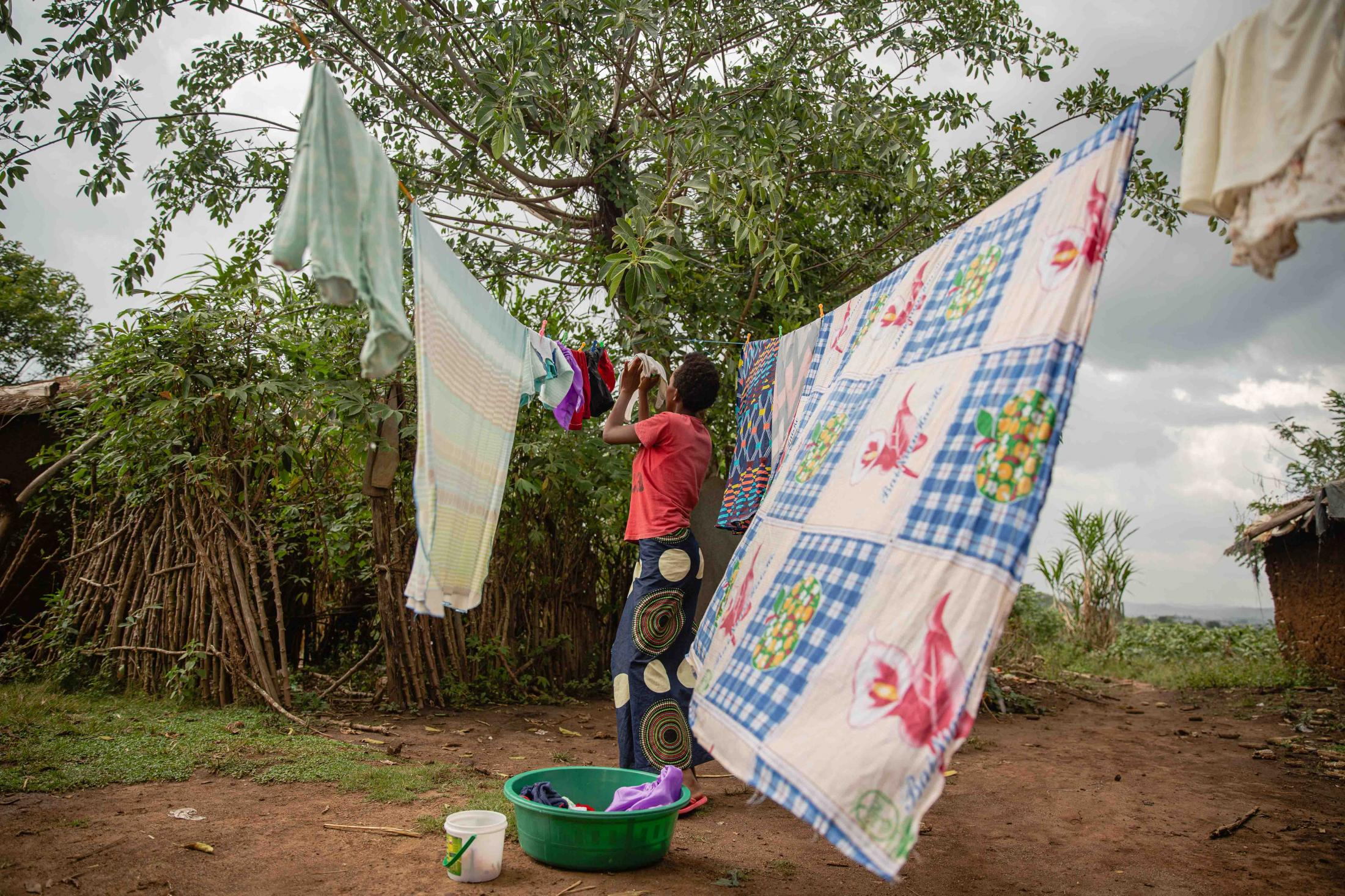 Lydia* hangs her baby's clothes at their home in Kyaka II refugee settlement. For Save The Children UK.
