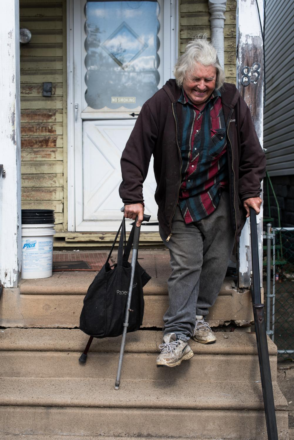 "John Lapinsky, a former Wheeling-area machinist, bears the pain of arthritis to descend his front stairs on Wheeling Island. Lapinsky remembers when the Ohio Valley's manufacturing base was stronger and when local plants regularly worked with cast iron and steel rolls weighing 350 tons. ""I retired a couple of years before it all started happening around here. I was lucky,"" he says."