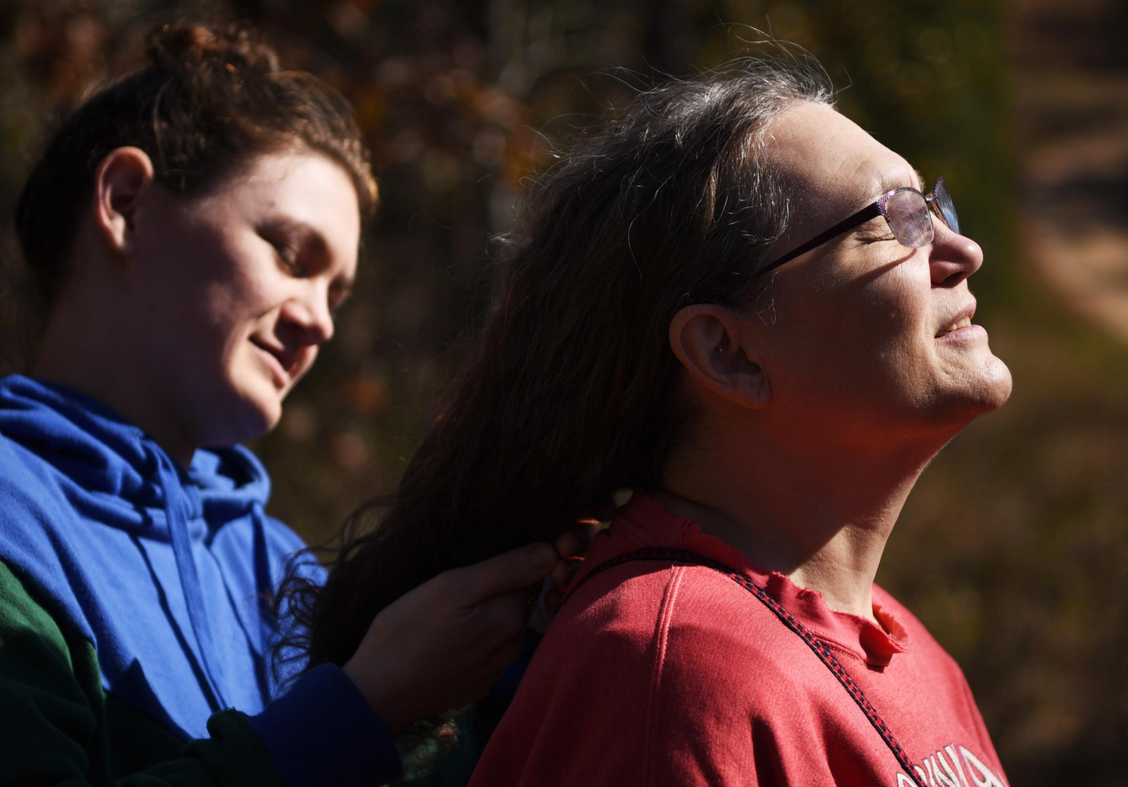 """Margaret Waddell soaks in the sun and warmth as Hannah Satterwhite pulls back her mother's hair on their land at Crystal Lake on Nov. 3, 2019. The property has been in Waddell's family for 5 generations. """"This is the first place I have ever truly felt at peace with myself,"""" Waddell said. """"Staying connected to nature and my ancestors is what makes me feel whole."""""""