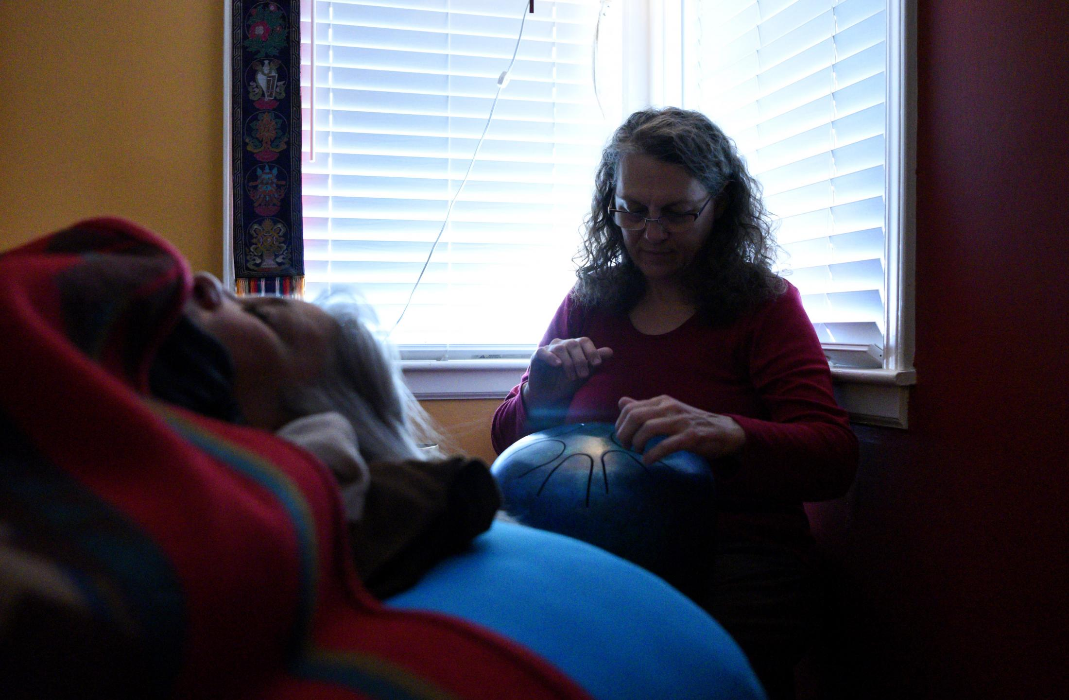 """Margaret Waddell plays the steel tongue drum in a sound healing session for a woman suffering from excessive migraines at Hummingbird Studio in Columbia, Missouri on Nov. 8, 2019. Sound and music have been used since ancient times for healing and transformation. Everything is vibration and you tune your body like you tune an instrument - Sound healing allows your body to heal itself by slowing down your brain waves, which affect every cell in your body, shifting them from diseased to be in ease. """"It is the most beautiful holistic experience,"""" the woman said, """"I always feel so much more at peace after my session."""""""
