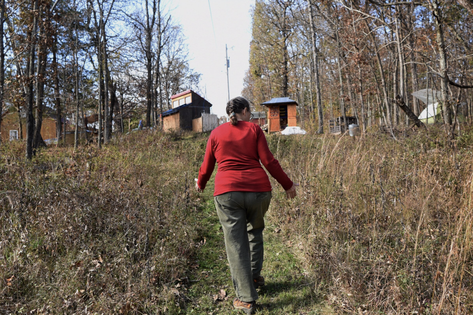 """Margaret Waddell walks toward the camping ground on her land at Crystal Lake on Nov. 3, 2019. The one-room cabin with a screened-in porch originally built on the land burned down in a fire 13 years ago. However, Waddell has spent as many weekends as possible camping and working on the land in an effort to rebuild her favorite place by hand. """"I have always wanted to rebuild the cabin in the spirit of my great-grandparents,"""" Waddell said. """"It is the greatest goal of my life to create a place where family and friends can gather to spend time together in nature... which inspires music and storytelling and a sense of community."""""""