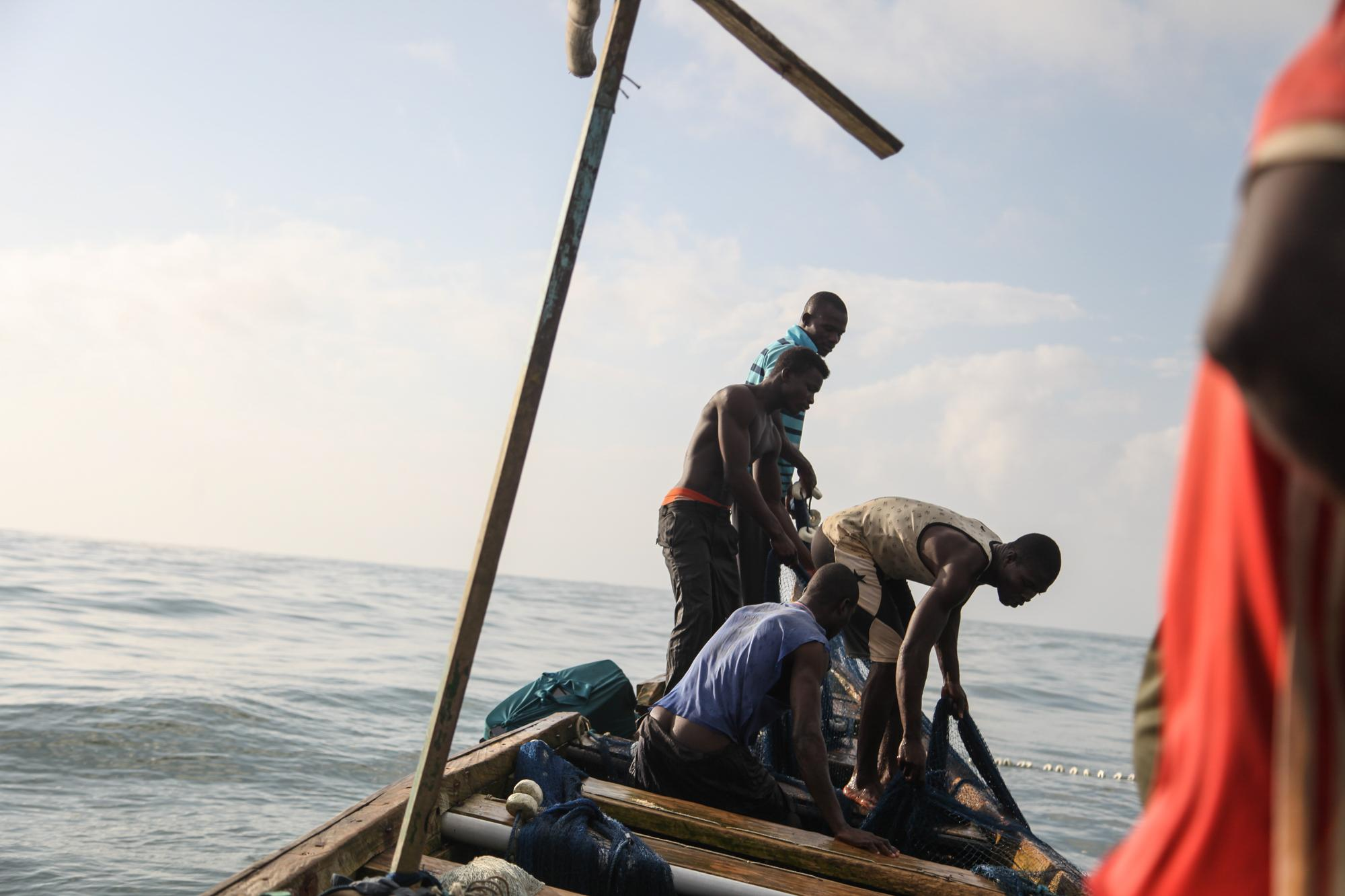 Fishermen pilling nets on the small wooden canoe in the Gulf of Guinea.