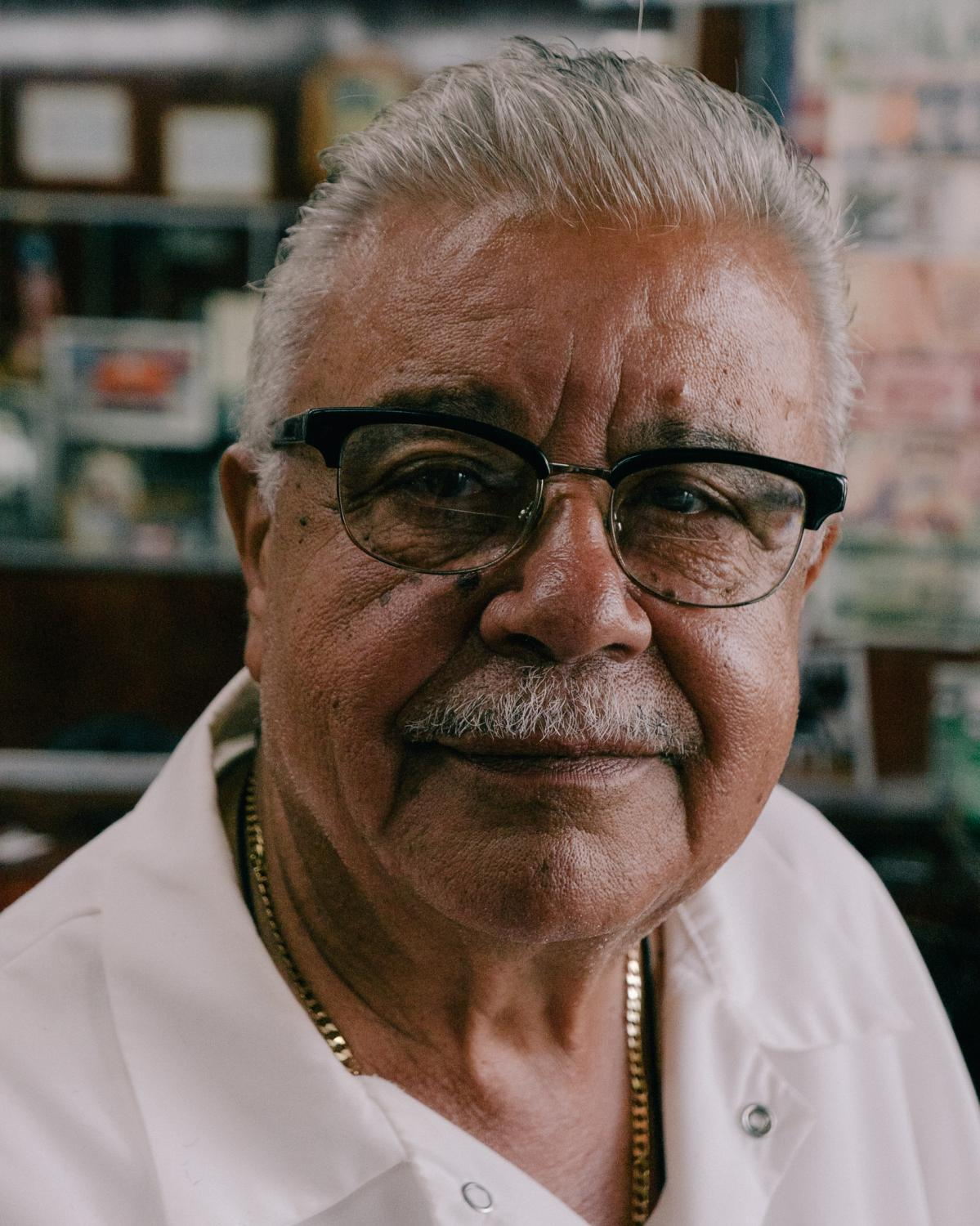 Eladio Burgos, 77, sits for a portrait as he waits for customers at his one seat barbershop on Suydam Avenue in the Brooklyn borough of New York City.